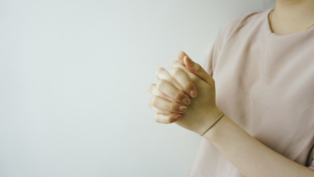 person wearing pink crew-neck shirt with hand clasped together