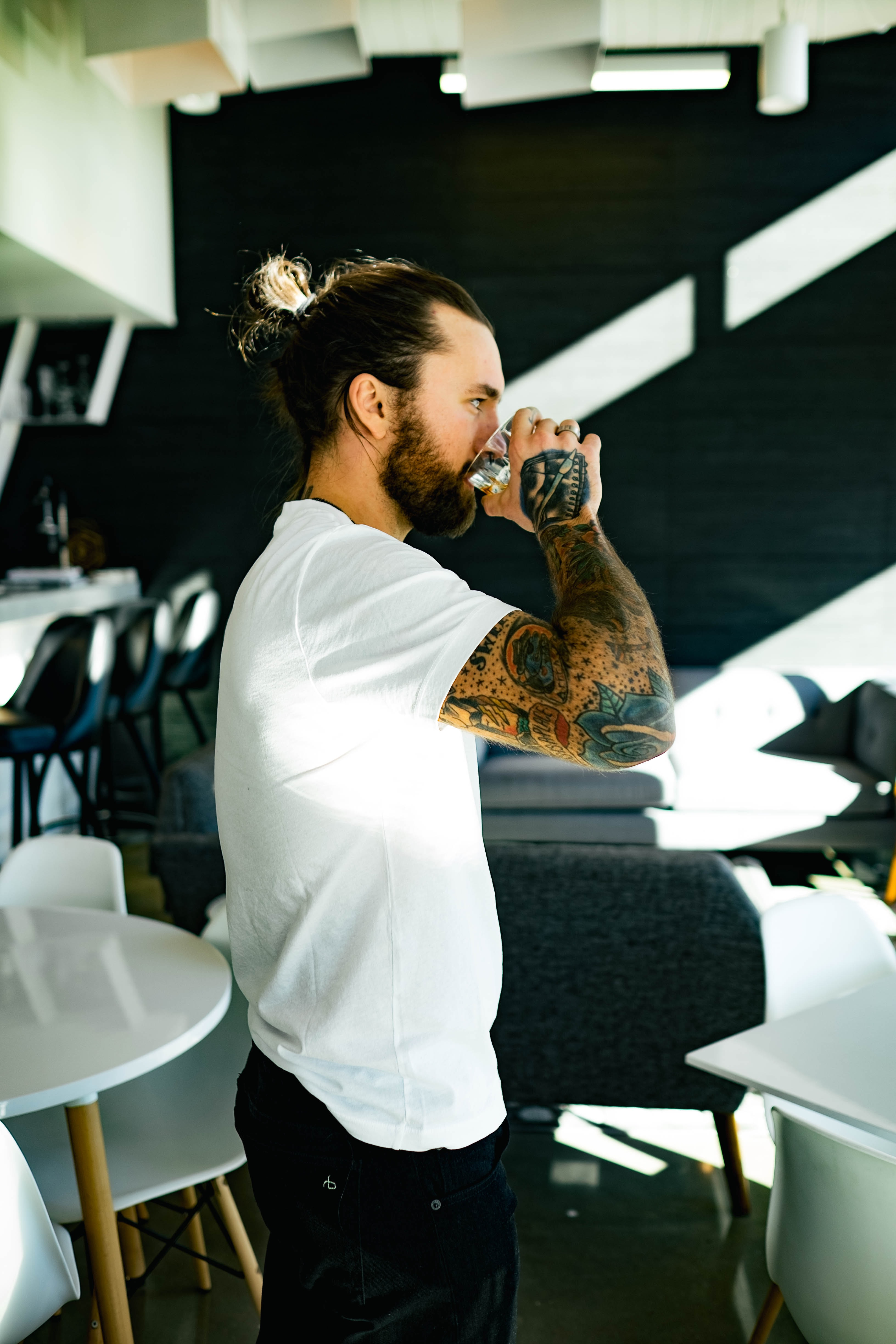 Man with colorful arm tattoos taking a sip from a glass while standing in a restaurant