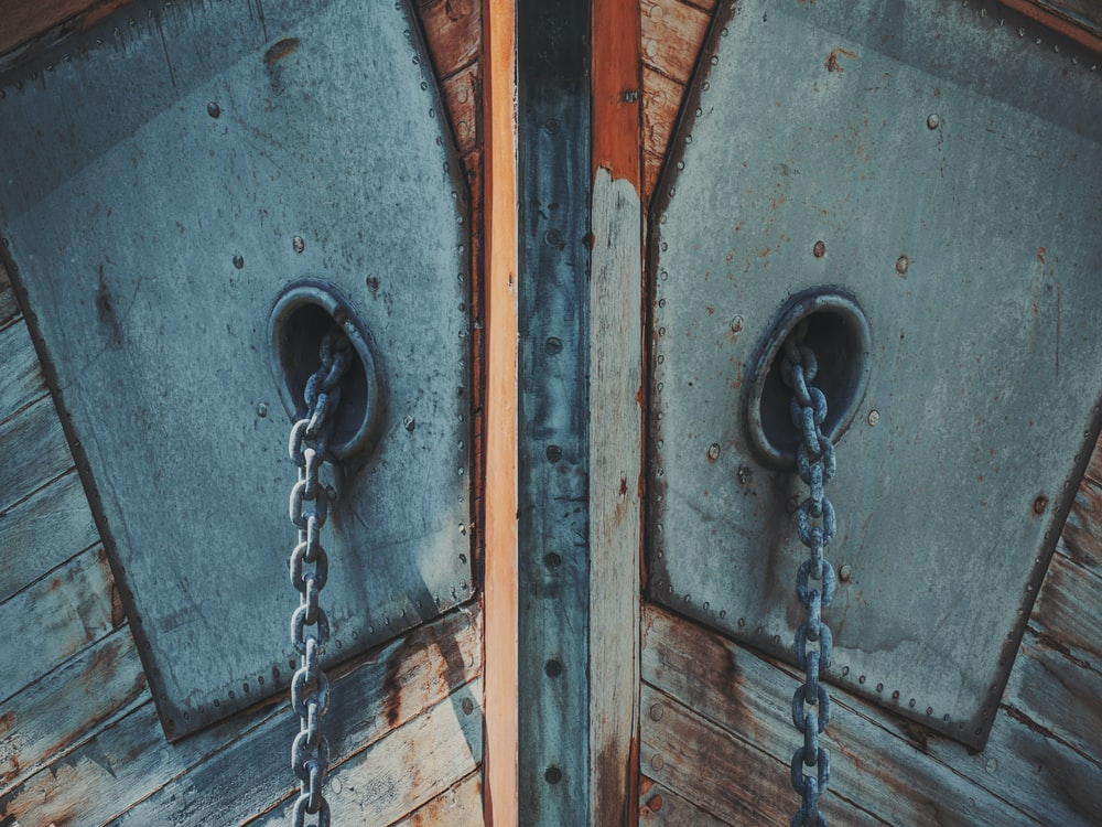 gray metal chains hanging from brown wooden surface