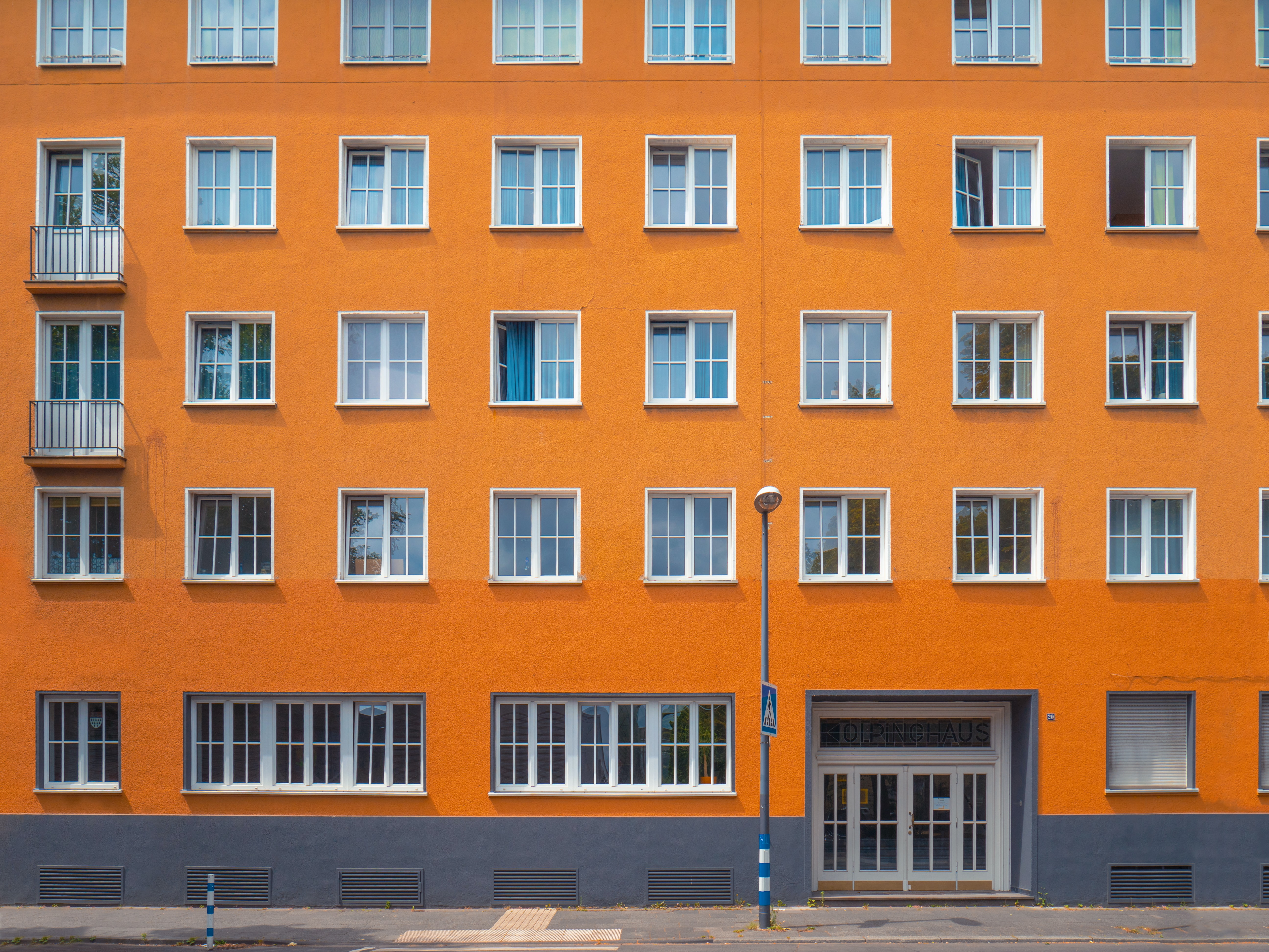 Street view of orange building in Cologne with white doors and windows