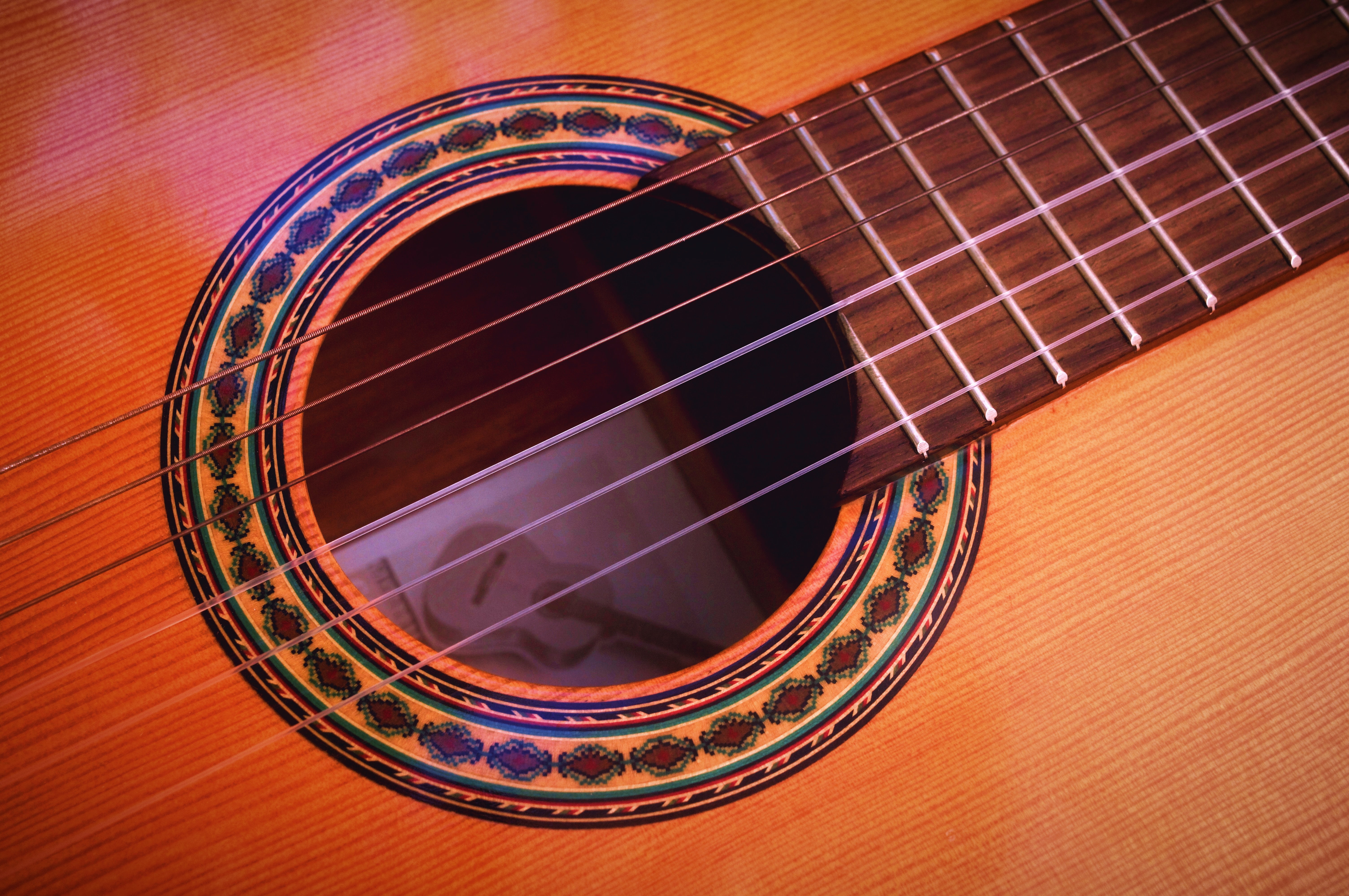 Macro of acoustic guitar's sound hole with ornate detail around it