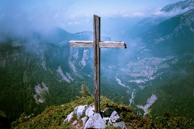 photo of brown wooden cross at cliff christianity teams background