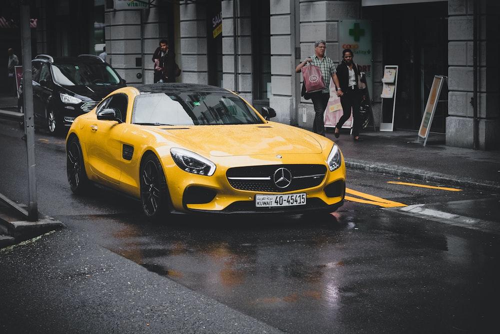 yellow Mercedes-Benz coupe on asphalt road near concrete building