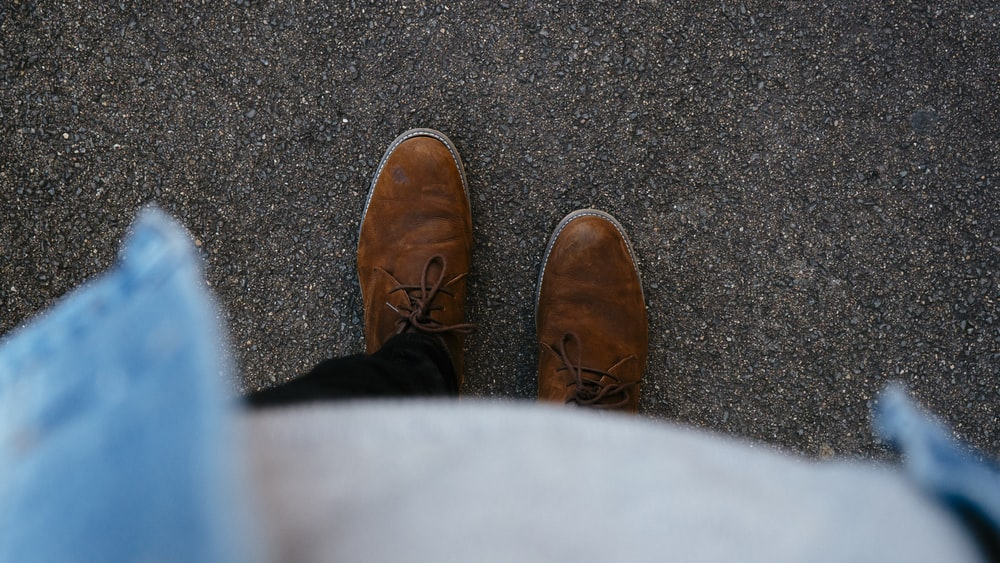 person wearing pair of brown leather boots standing on asphalt surface