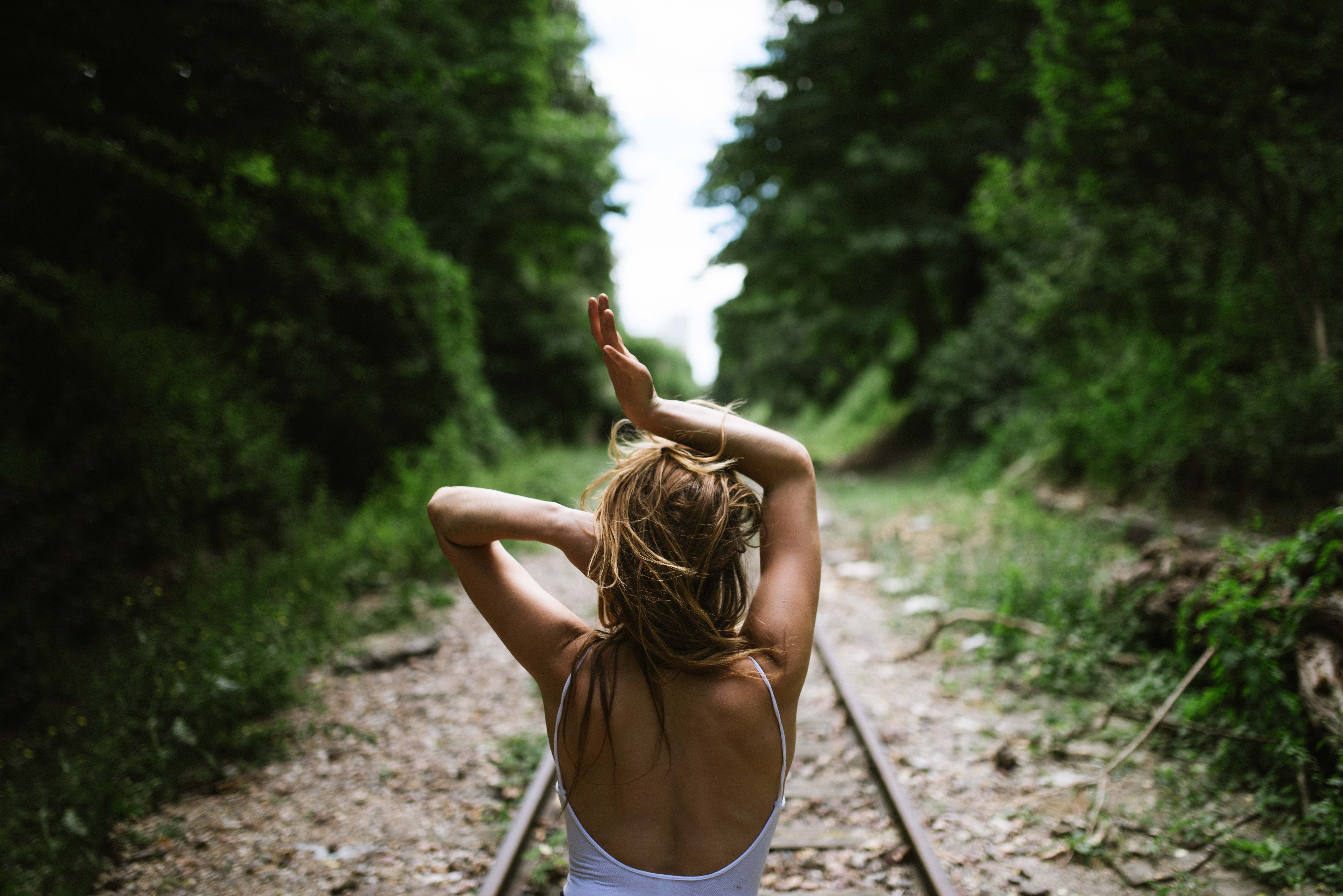 A woman faces away down outdoor train tracks in Paris with her arms over her head