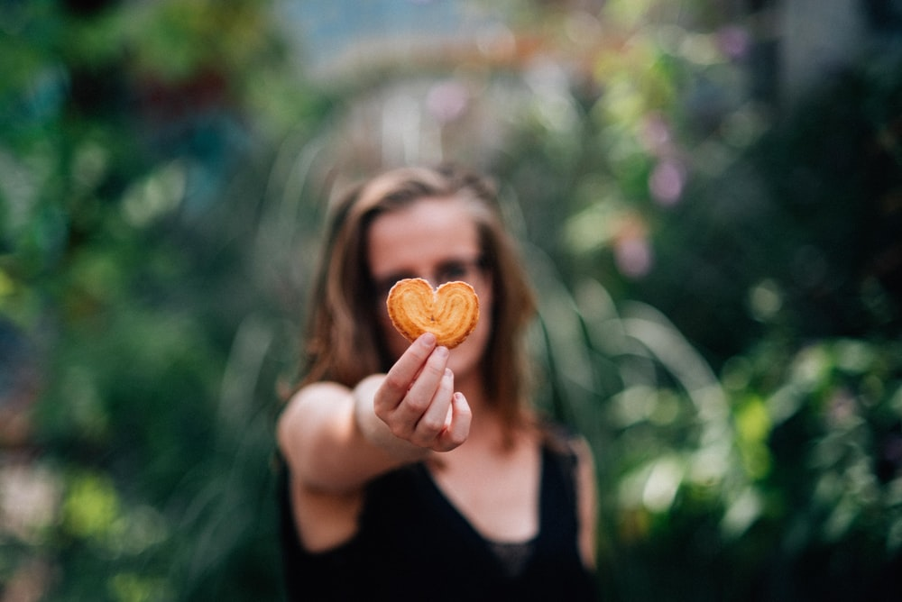 woman in black top holding heart shaped cookie
