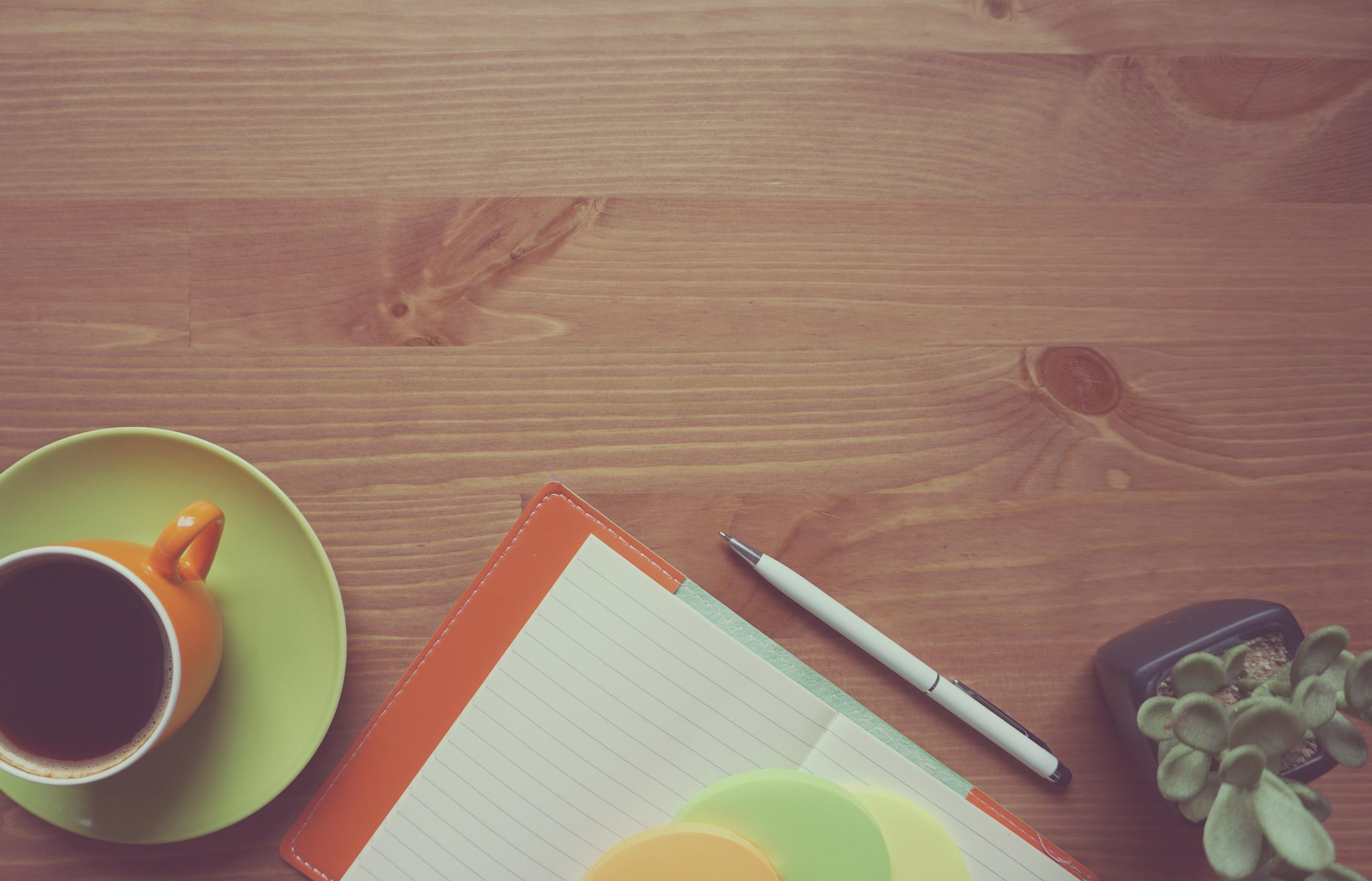 A cup of coffee beside a notebook, pen and bonsai tree