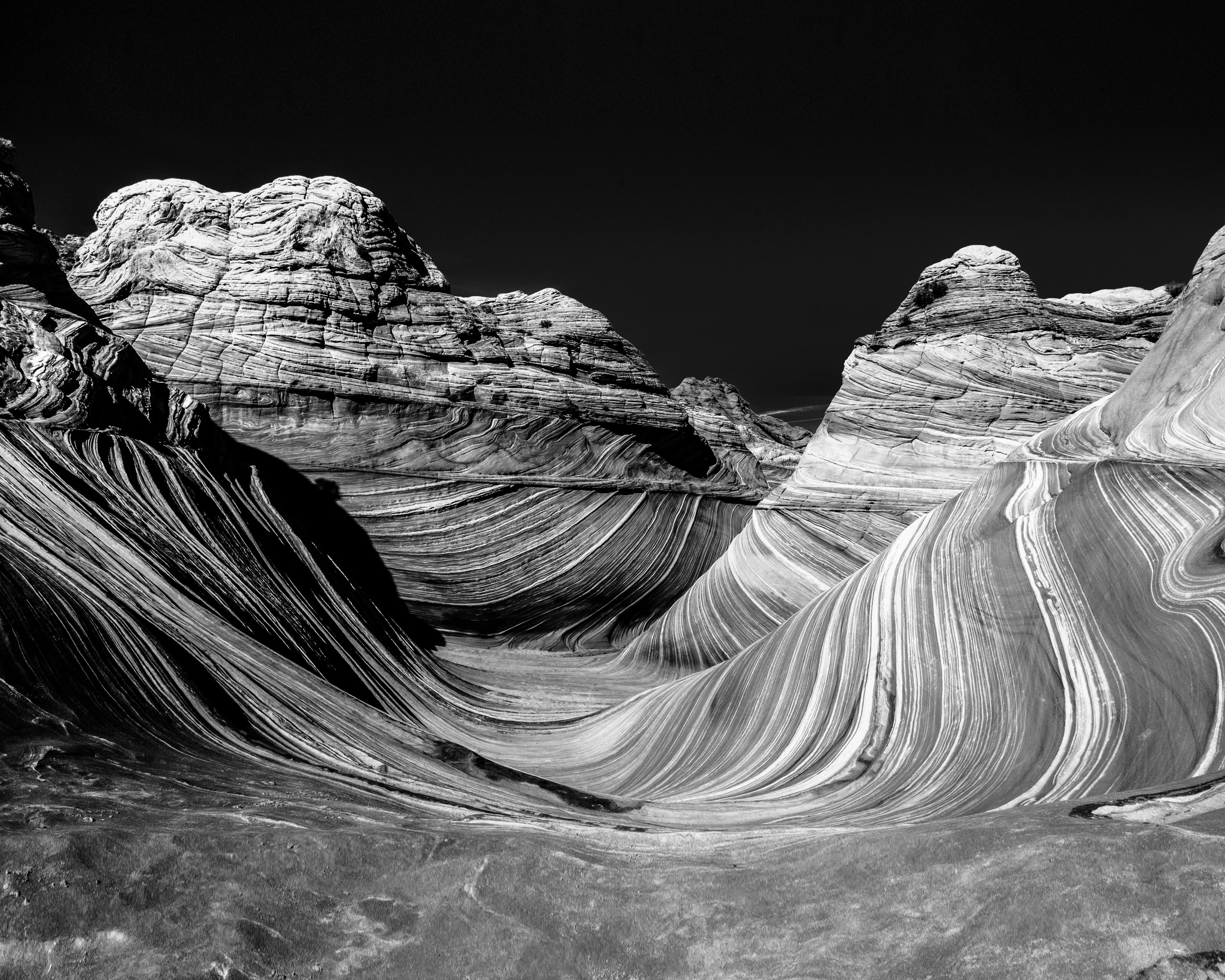 Sandstone forms wavy lines against rocky mountain formations