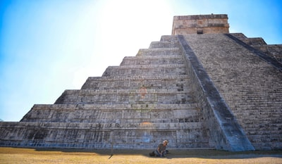 person sitting on grass field in front on gray concrete pyramid mayan pyramid teams background