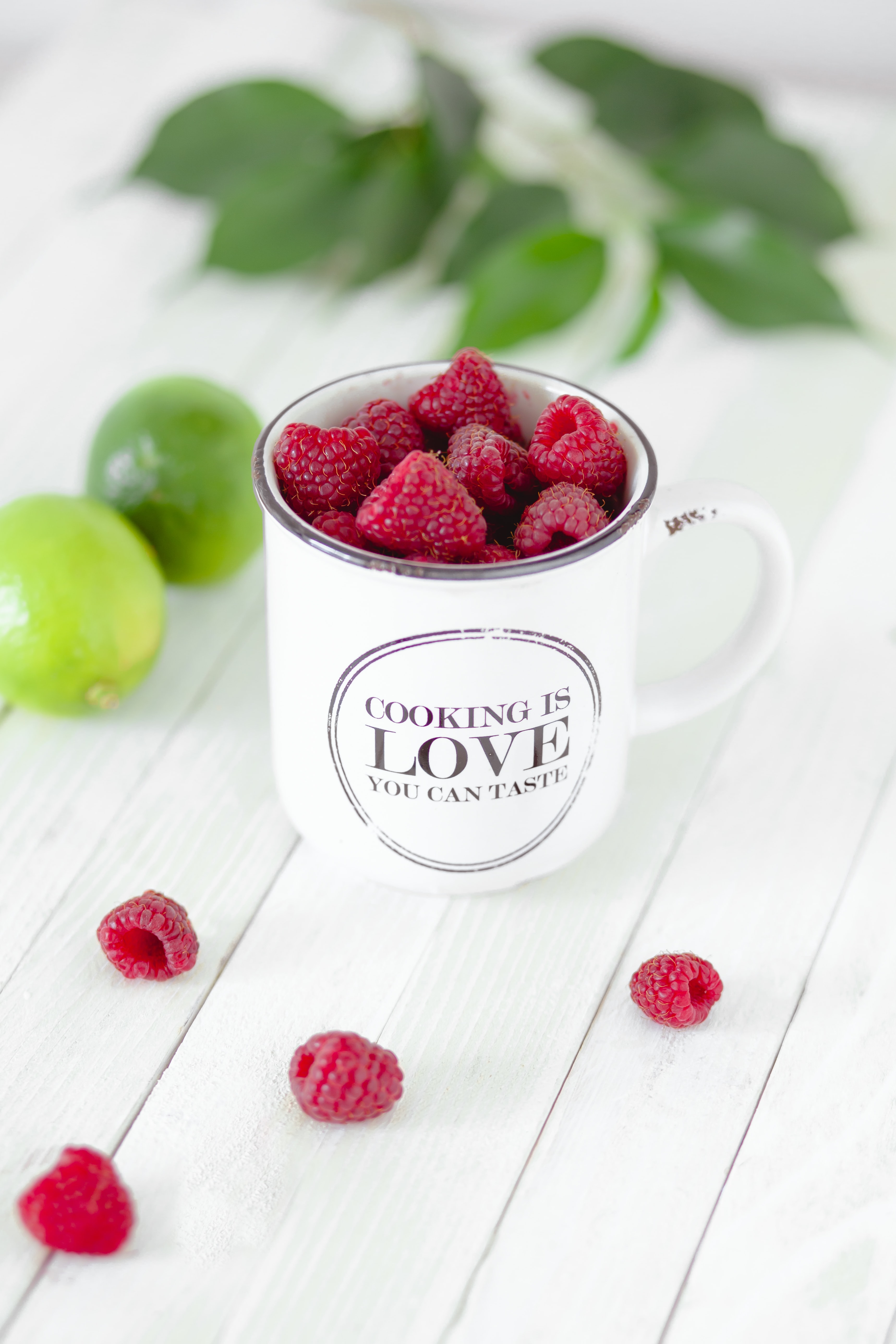 Mug of fresh raspberries on a table with limes and mint
