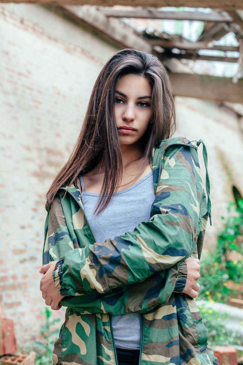 woman in gray spaghetti strap shirt and camouflage jacket