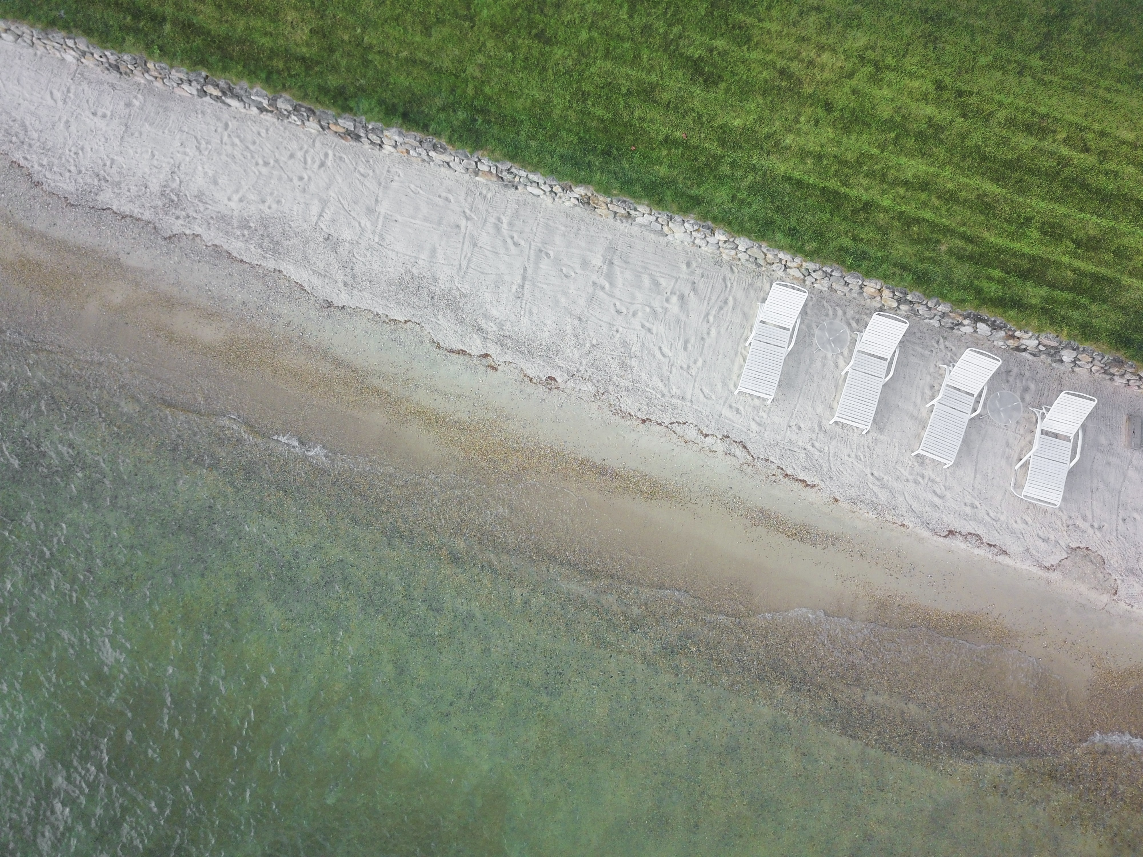 Drone aerial view of white beach chairs on a white sand shore strip with clear ocean