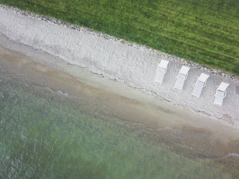 birds eye view of four white lounge chairs on white sand