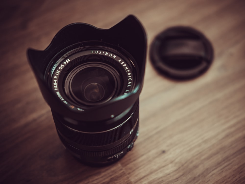 camera zoom lens with cover on brown wooden surface
