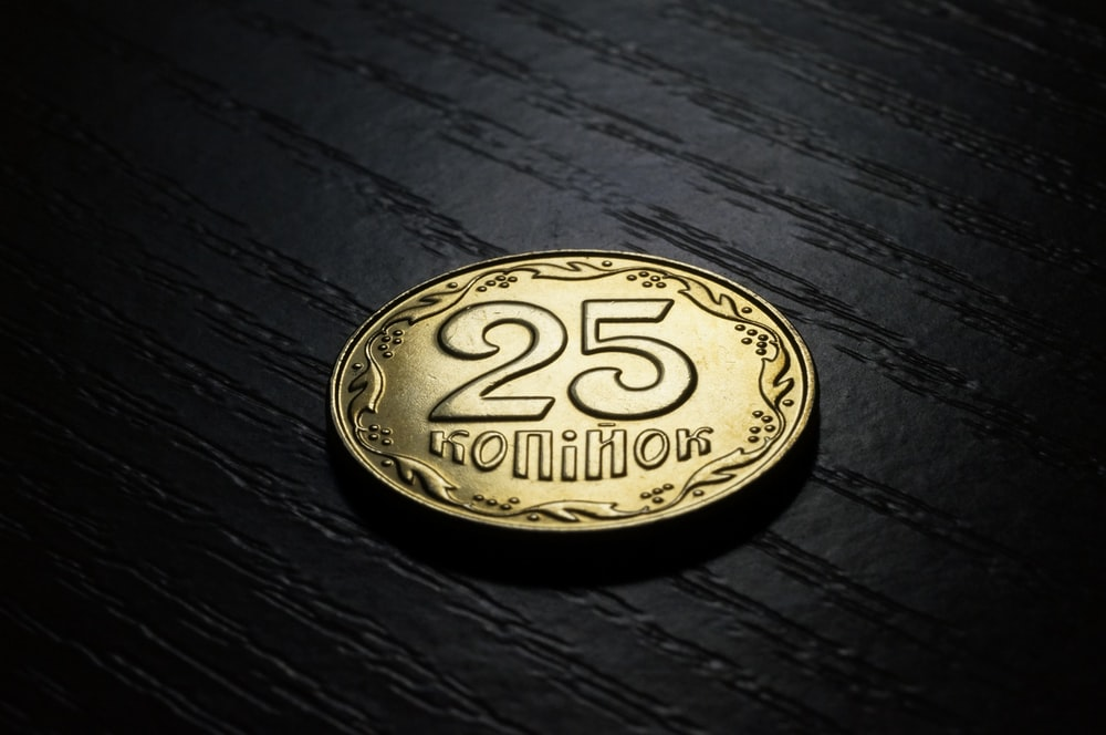 round gold-colored 25 con on black surface