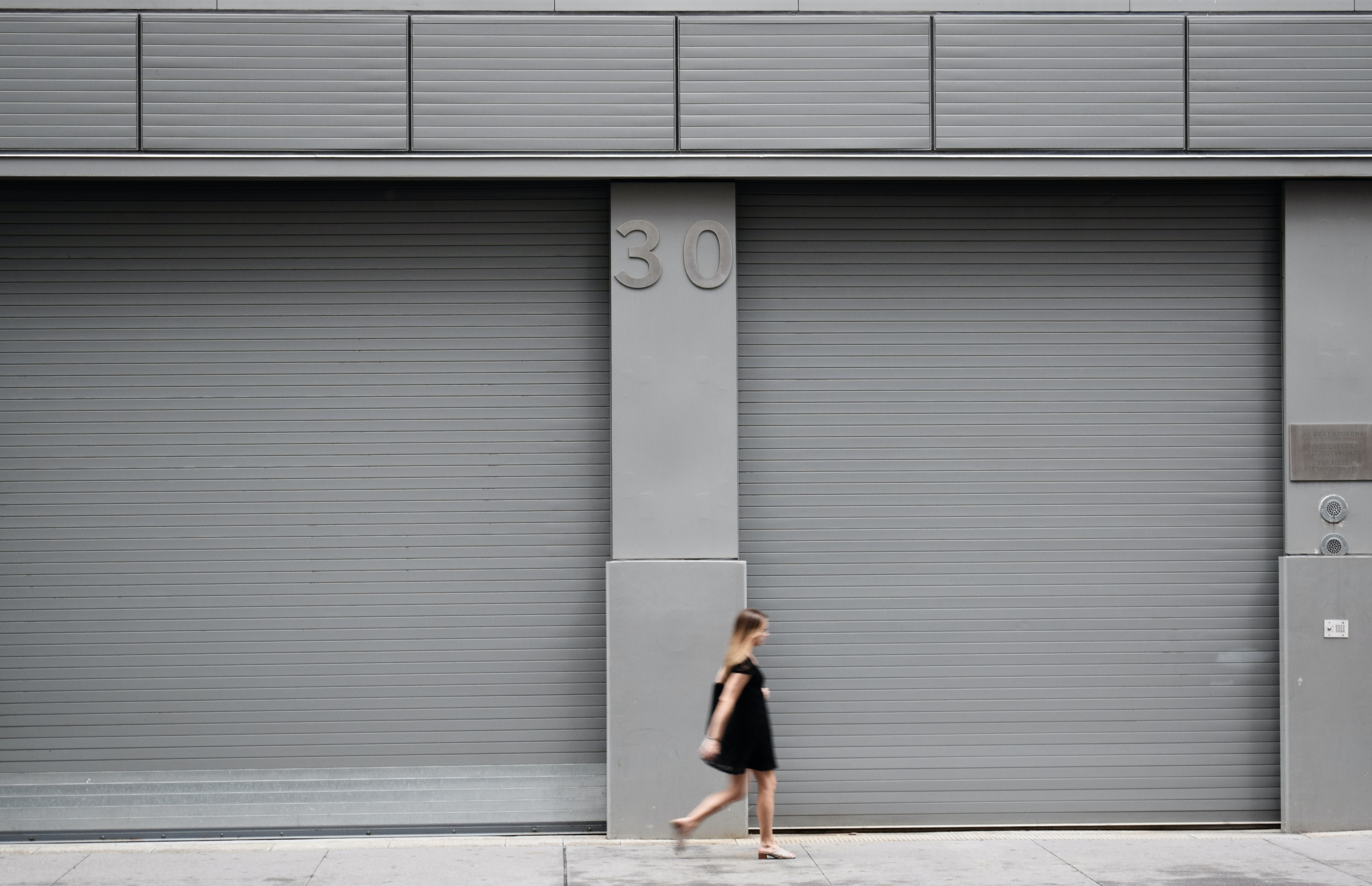 A woman walks along a gray colored building with the number 30.