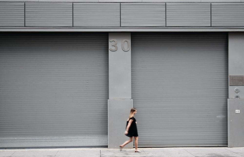 woman walking beside gray shutter door