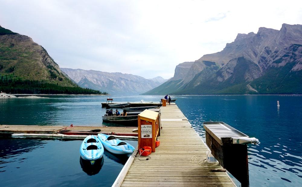 two blue kayaks beside brown wooden port