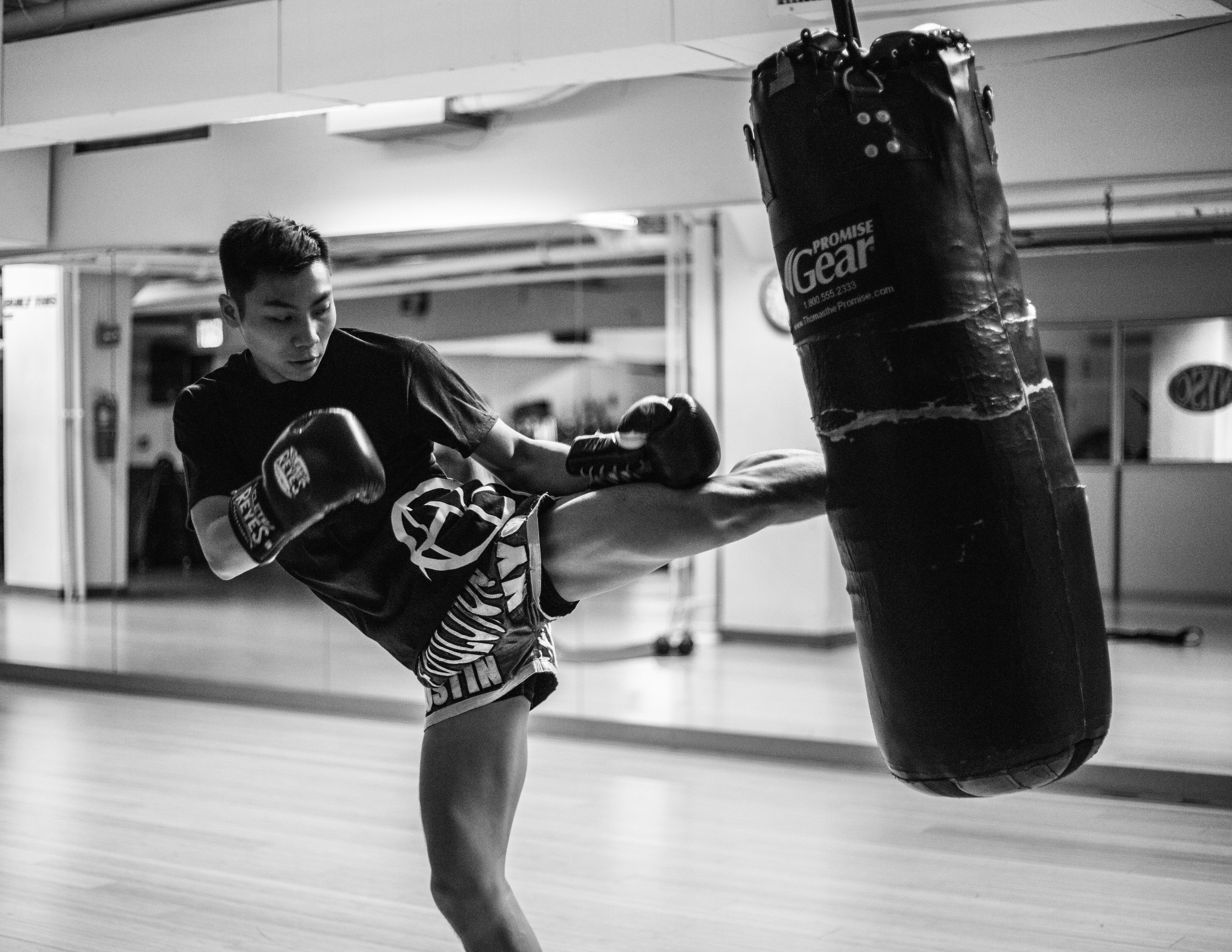 A man wearing boxing gloves, kicking a punching bag at a gym in Manhattan