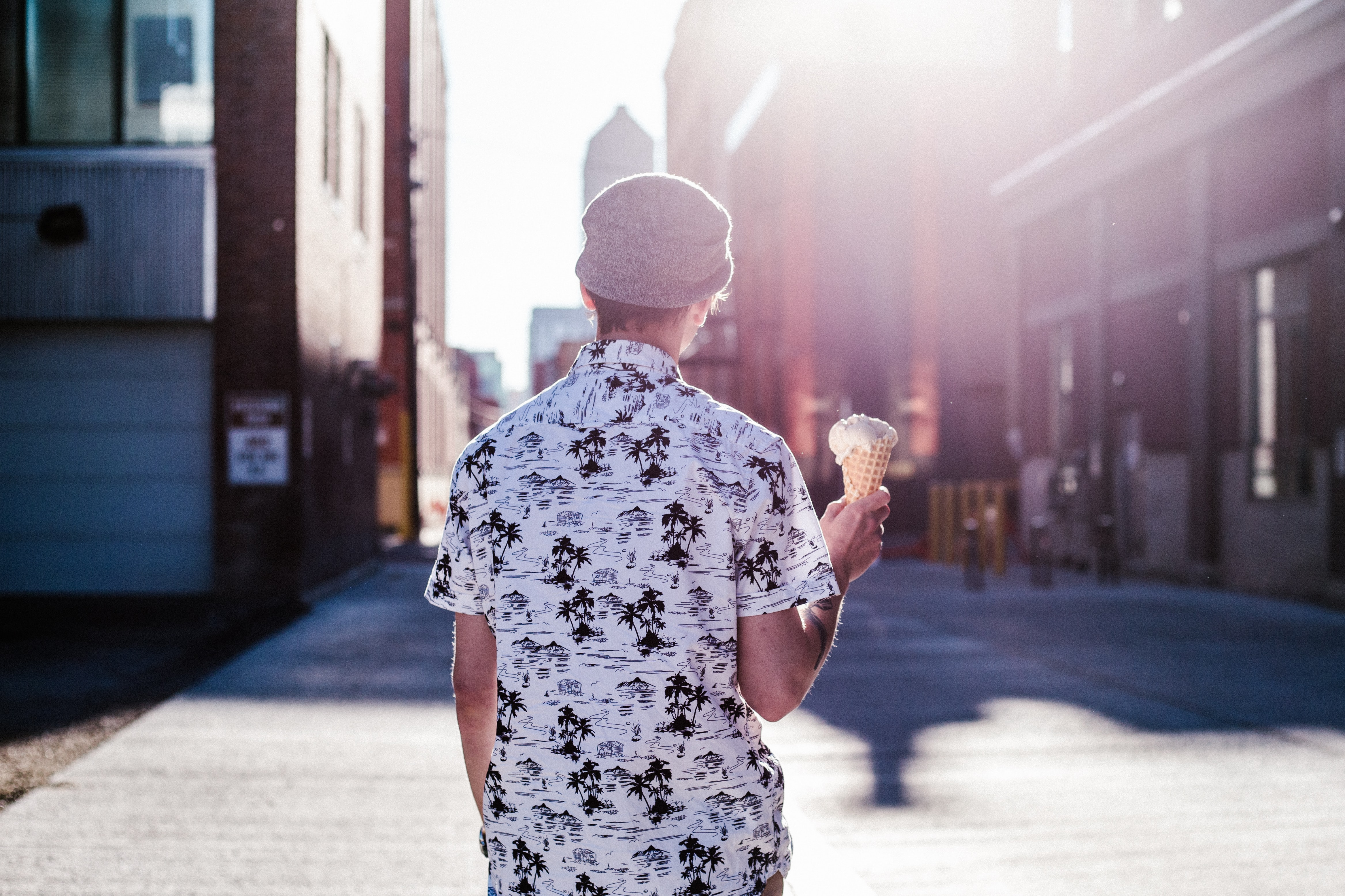 Person in a hat and tropical shirt holding an ice cream cone