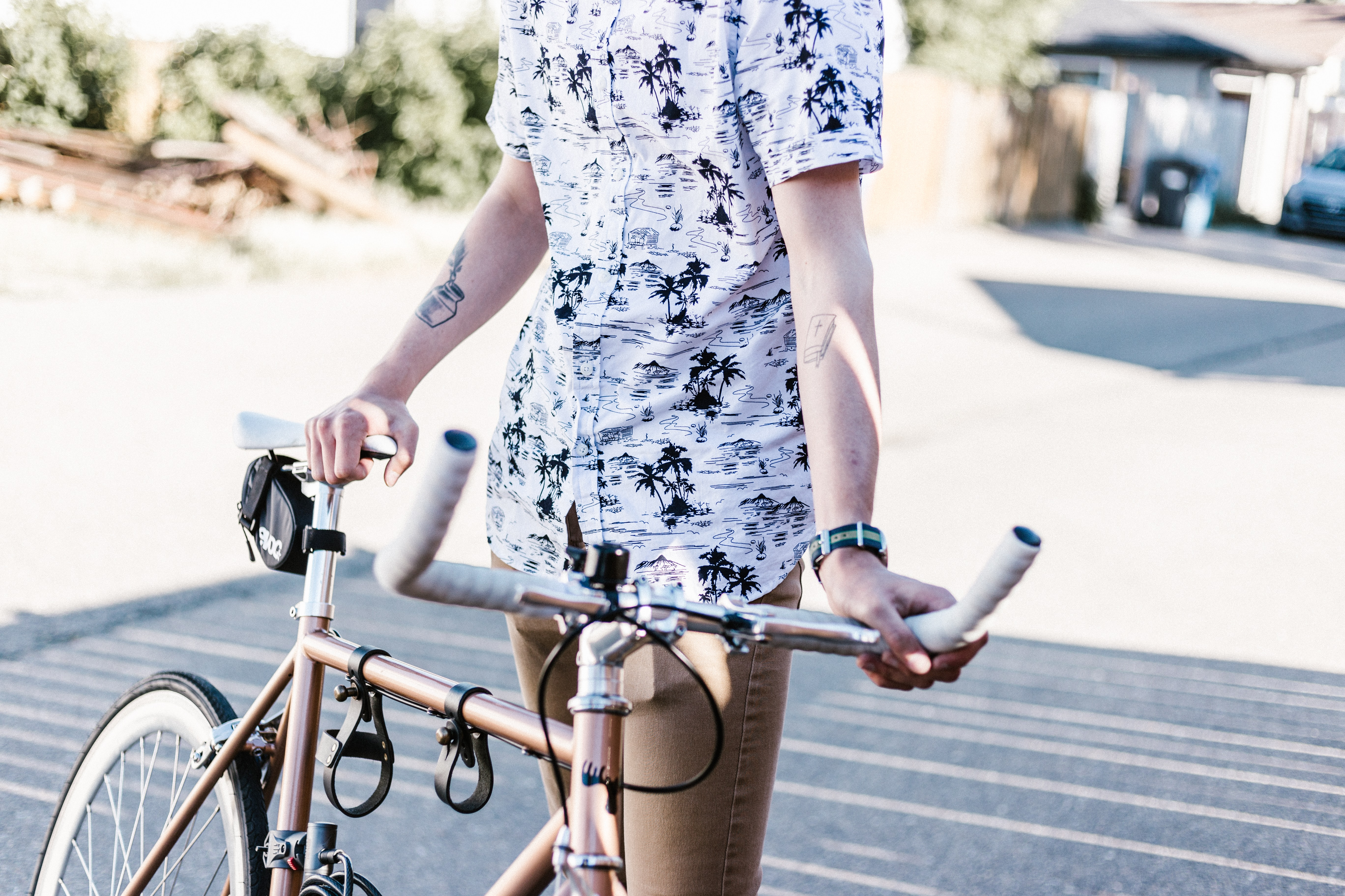 Man with tattoos wearing a fashionable pattern shirt holding his golden bike in the afternoon