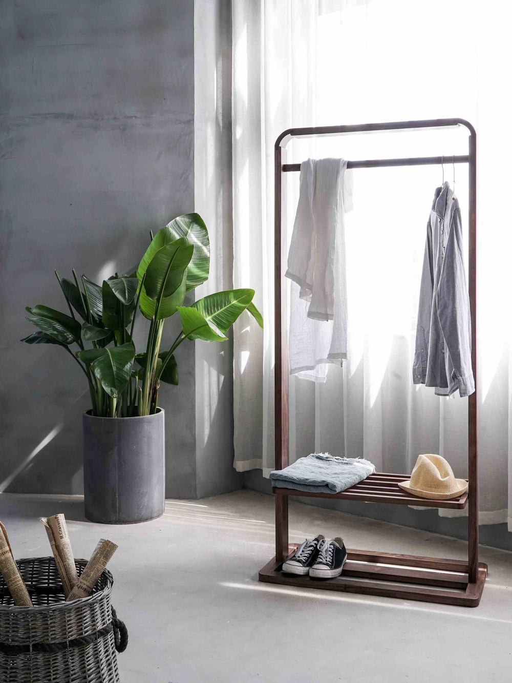 sustainable travel - gray dress shirt hang on brown wooden rack in front of window with white curtain