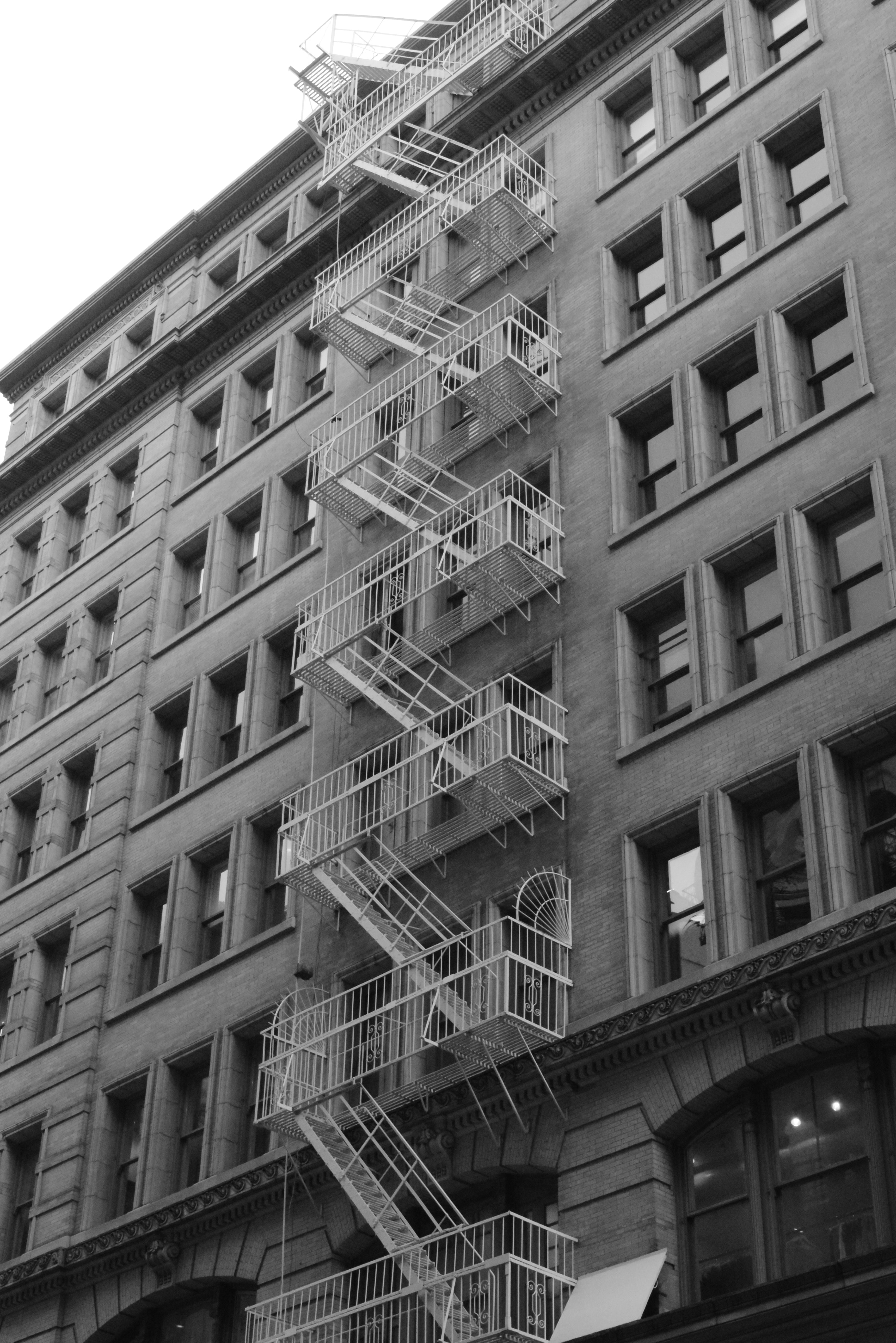 Black and white shot of urban apartment with windows and exterior fire escape