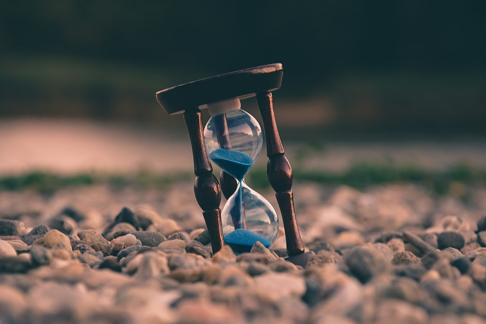Blue sand falls in an hourglass on a rocky beach
