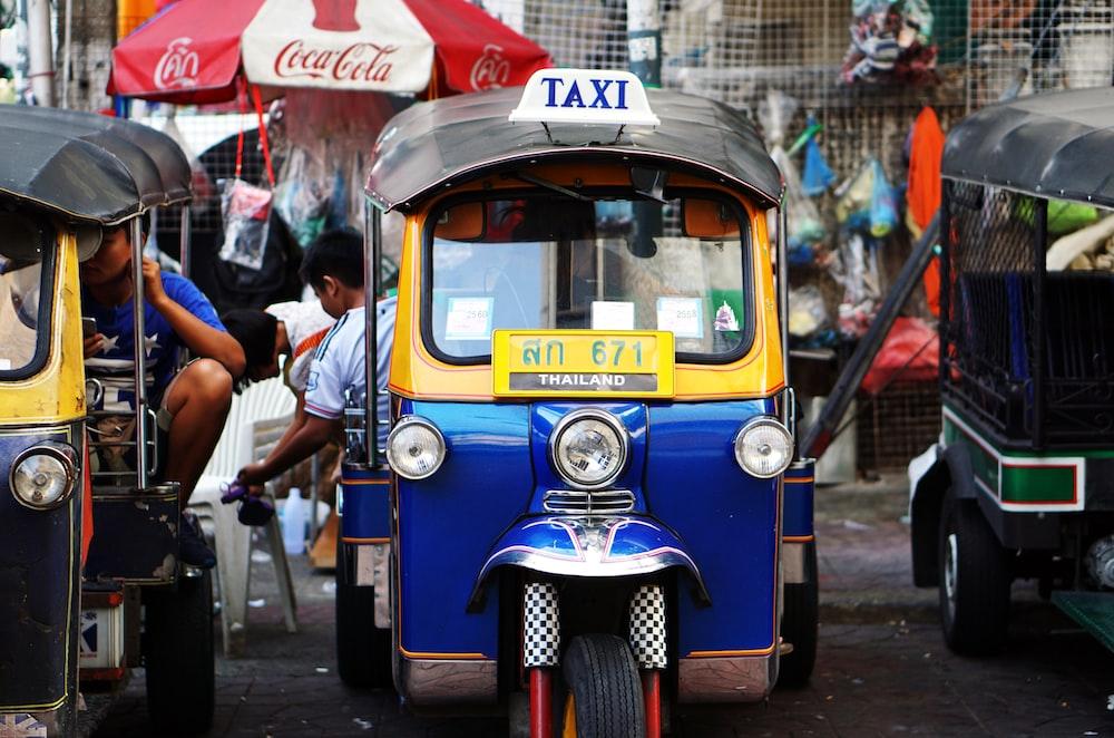 yellow and blue auto rickshaw parked beside auto rickshaw