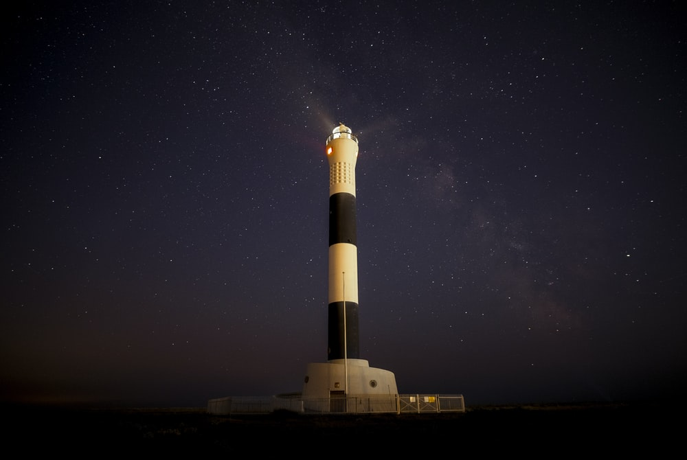 white and black lighthouse during nigh time