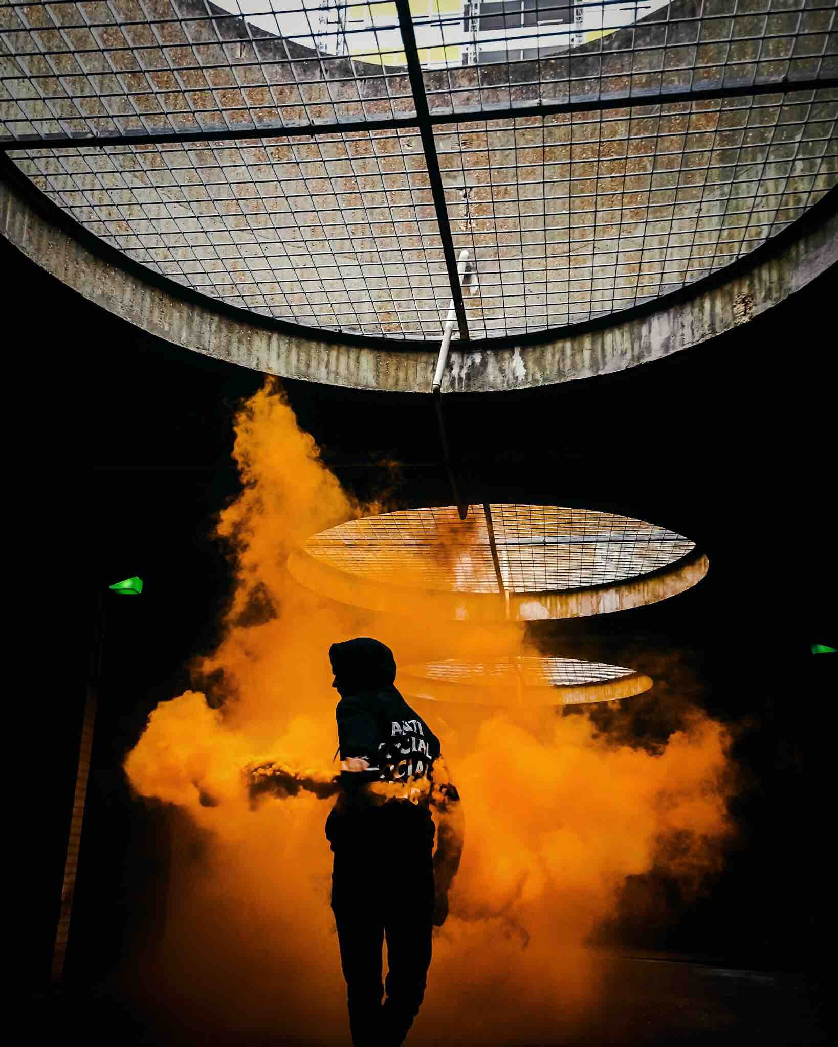 Silhouette of person in a hood running through orange smoke underground