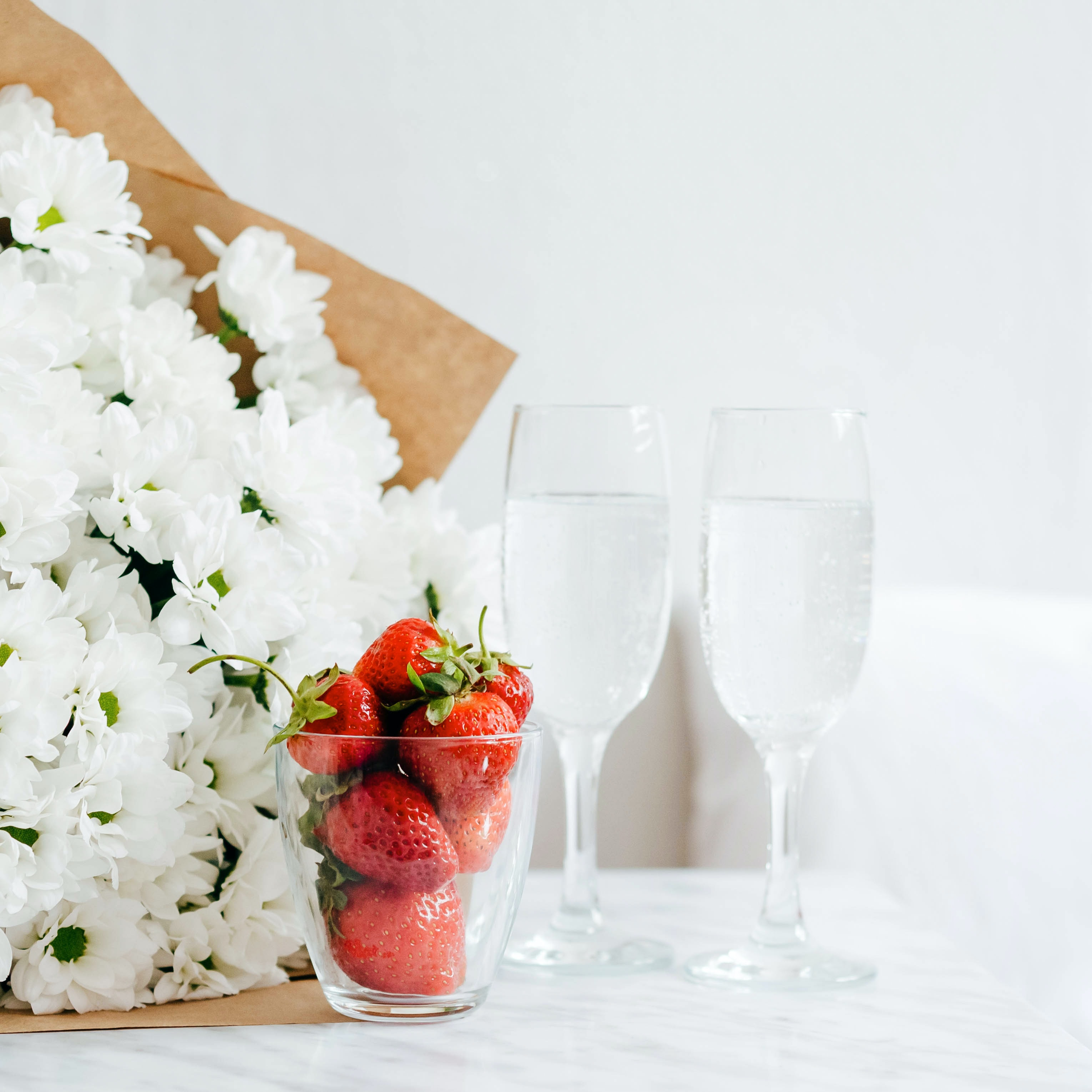 red strawberries filled glass cup beside white flower bouquet