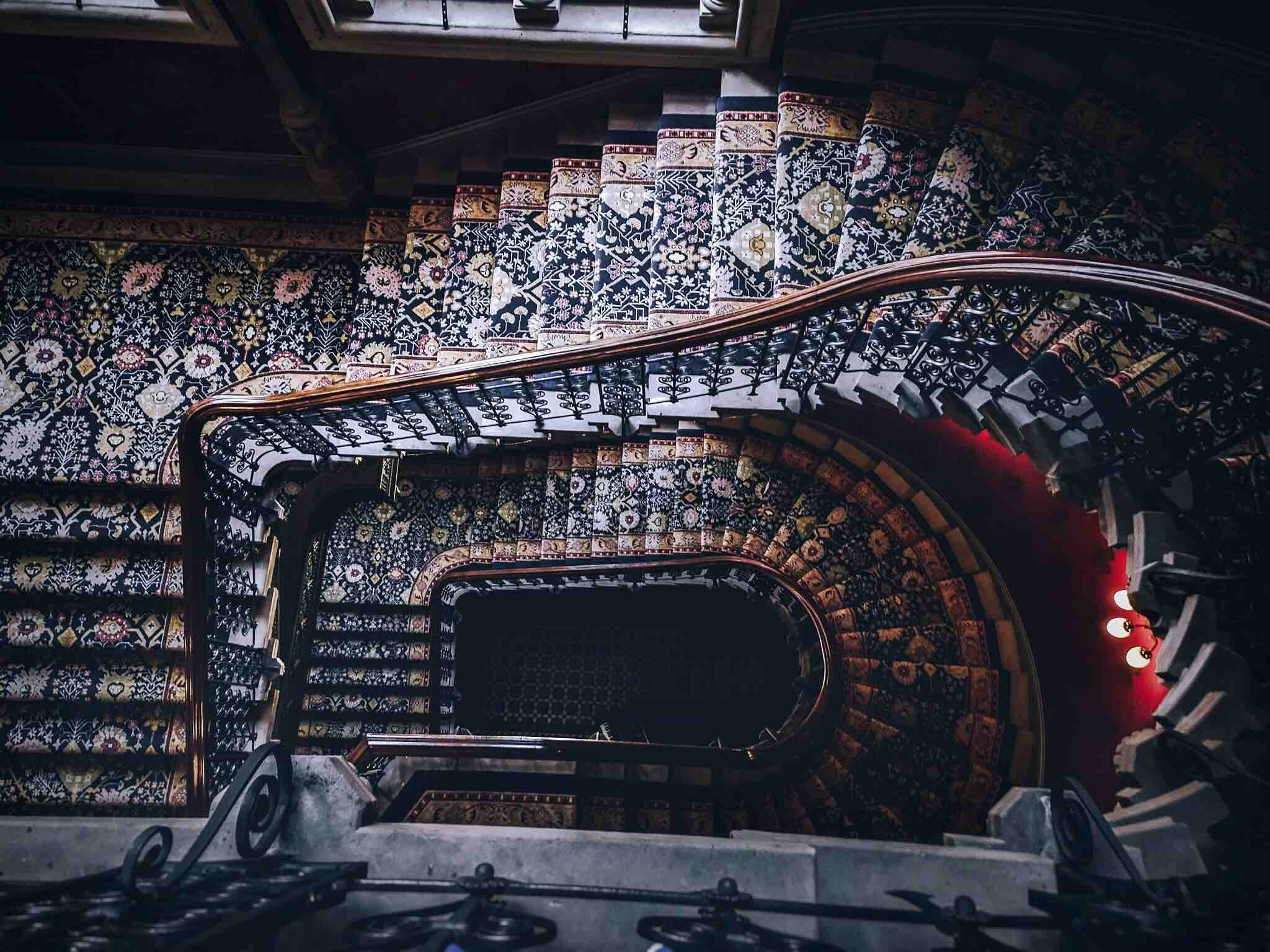A spiral staircase with ornate carpet and banister designs