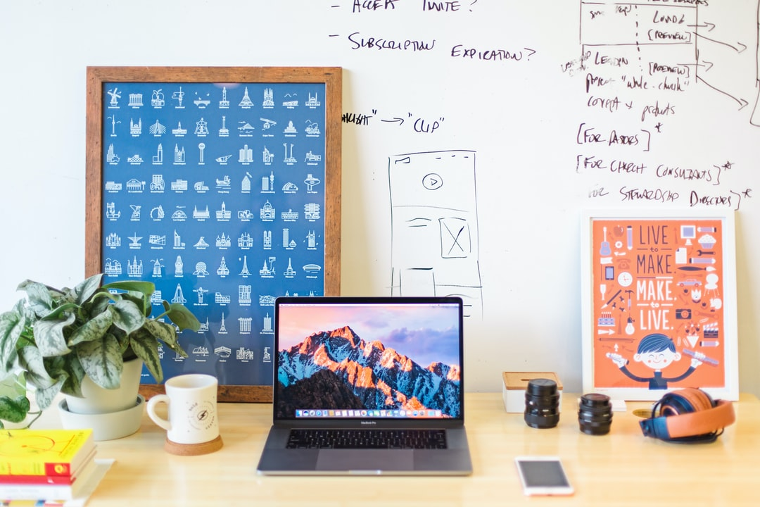 A workspace with a MacBook, two posters and drawings on the white wall