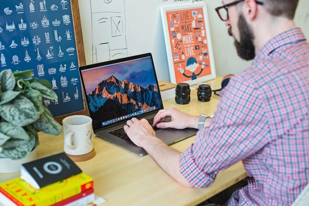 man wearing collared shirt using MacBook