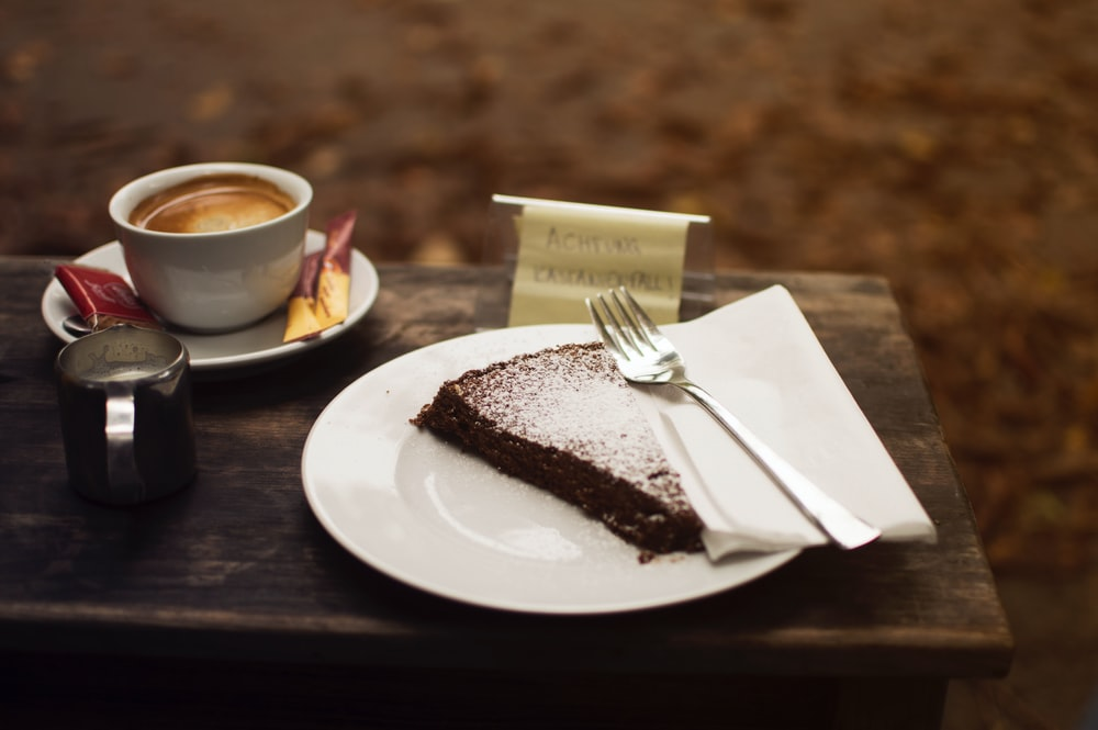 plate of sliced cake with silver fork beside cup of coffe on brown wooden serving board