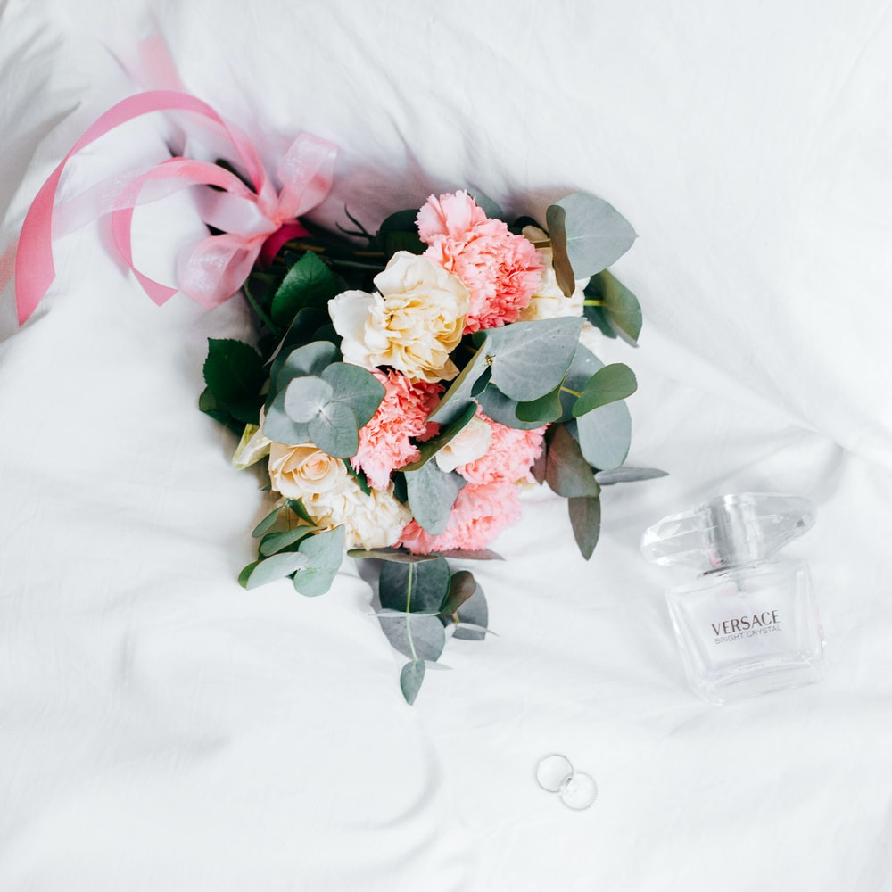 bouquet of yellow-and-pink roses and chrysanthemums placed next to Versace spray bottleon white textile
