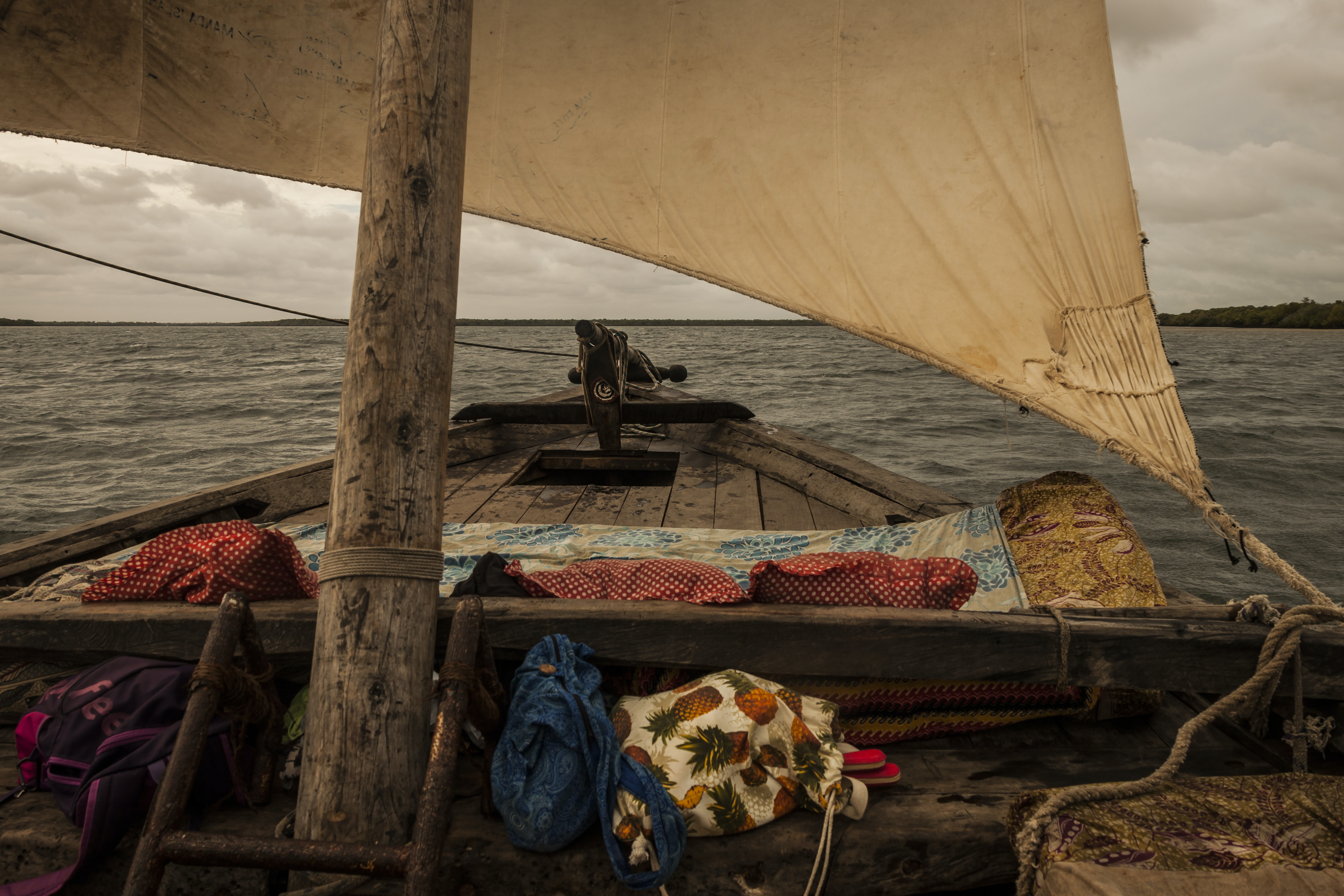 A pineapple tote bag and colorful shet on a sailboat deck in Lamu