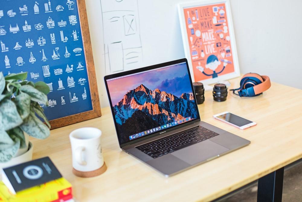 turned on MacBook Pro beside white ceramic mug