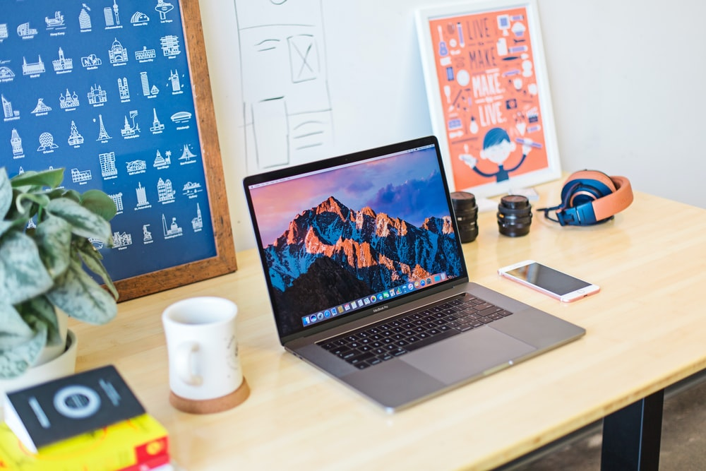 A creative workspace with a MacBook, a stack of books and two posters