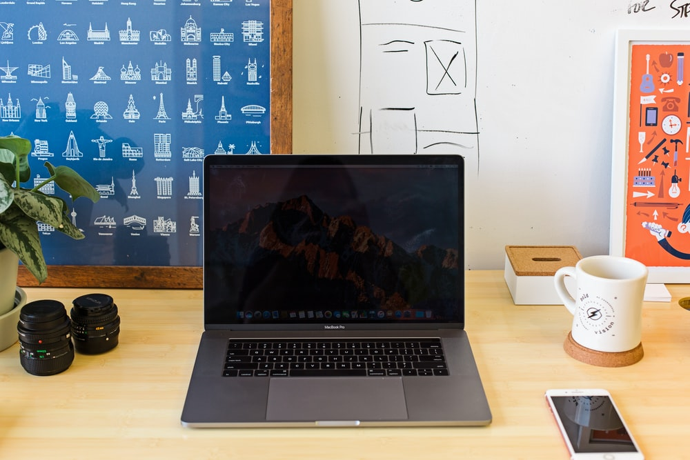 Macbook Pro on table near white mug and PRODUCT RED iPhone