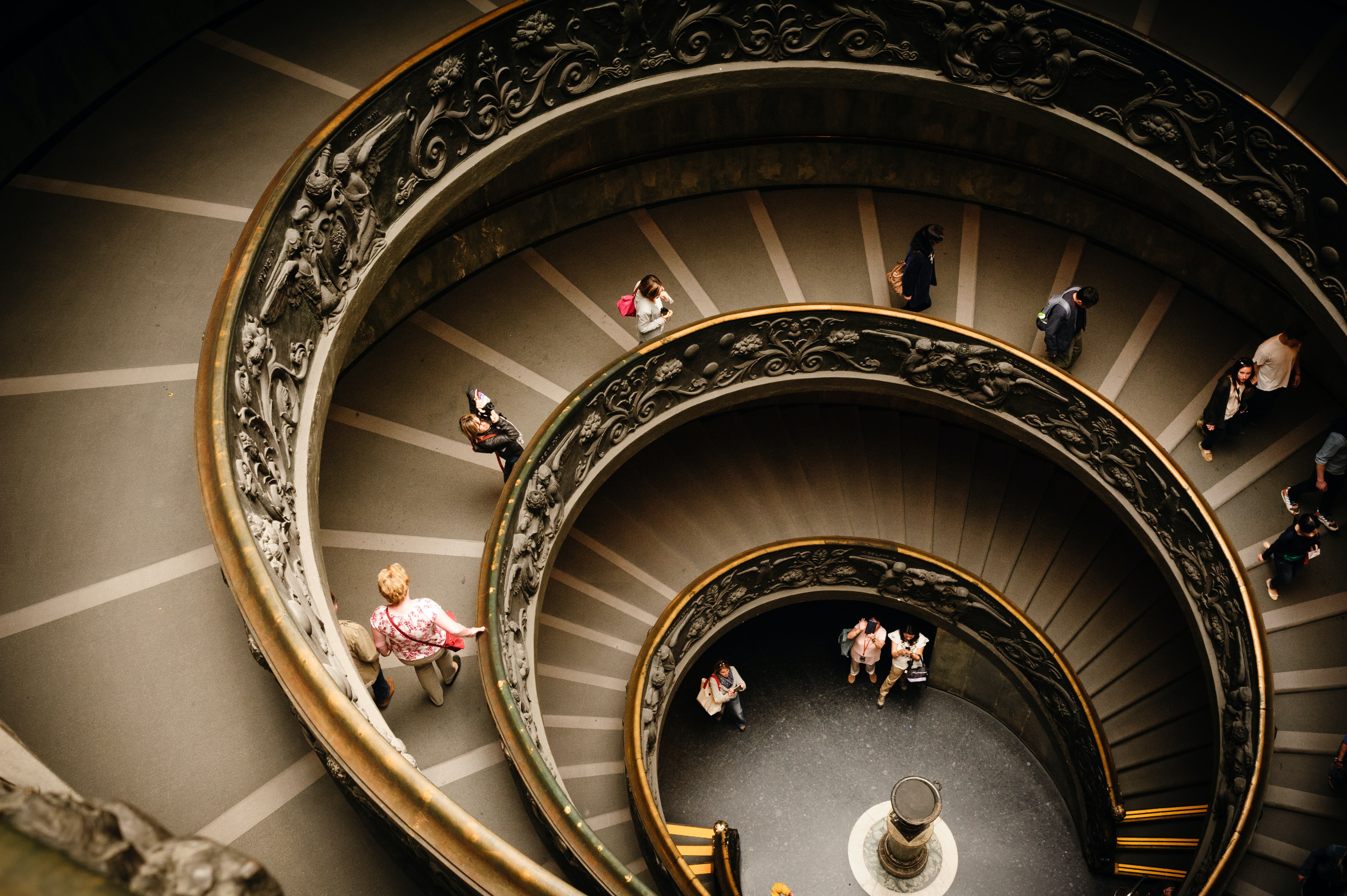 An overhead shot of people going down a spiral staircase