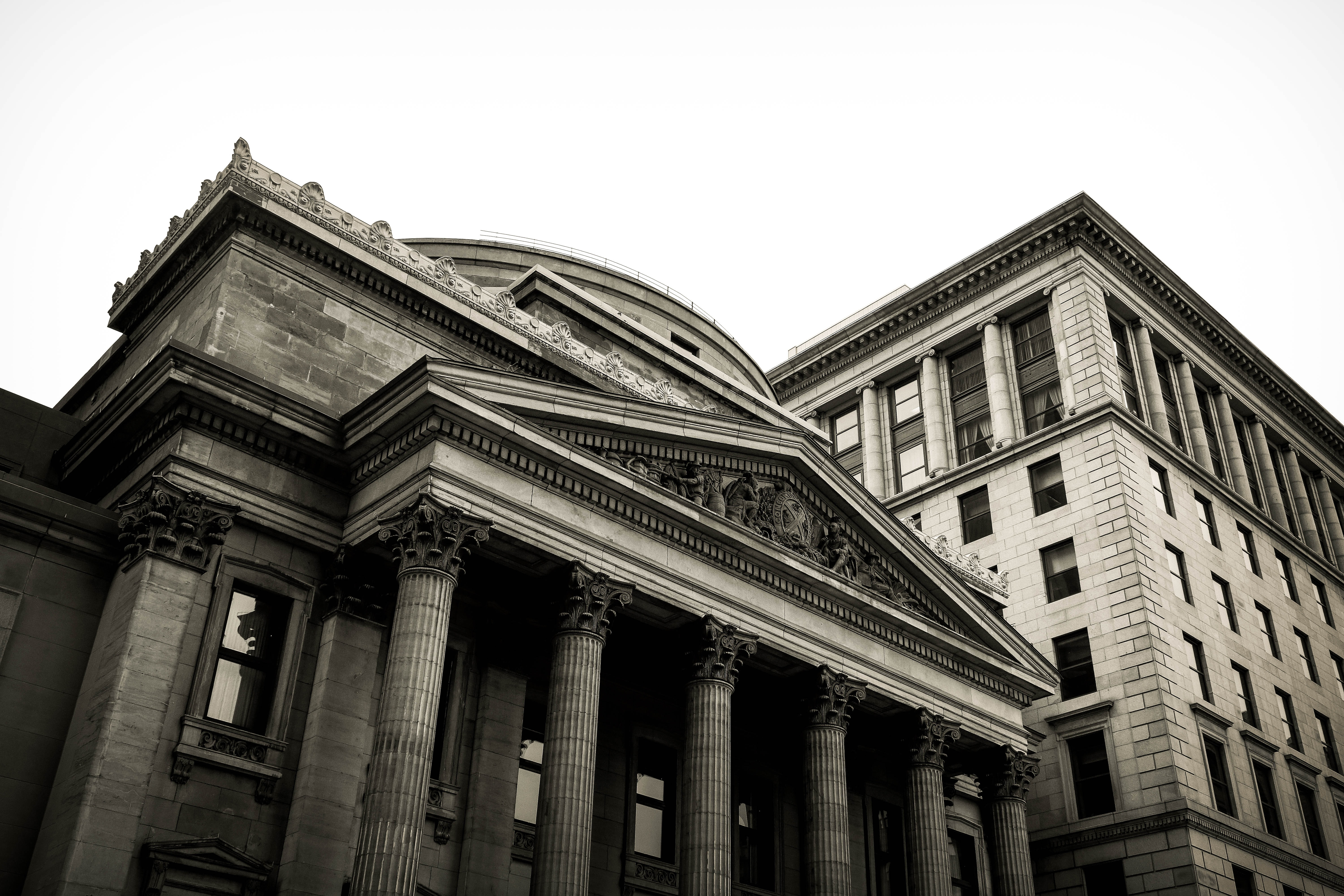 Black and white shot of historic building with columns in Montreal with clear sky