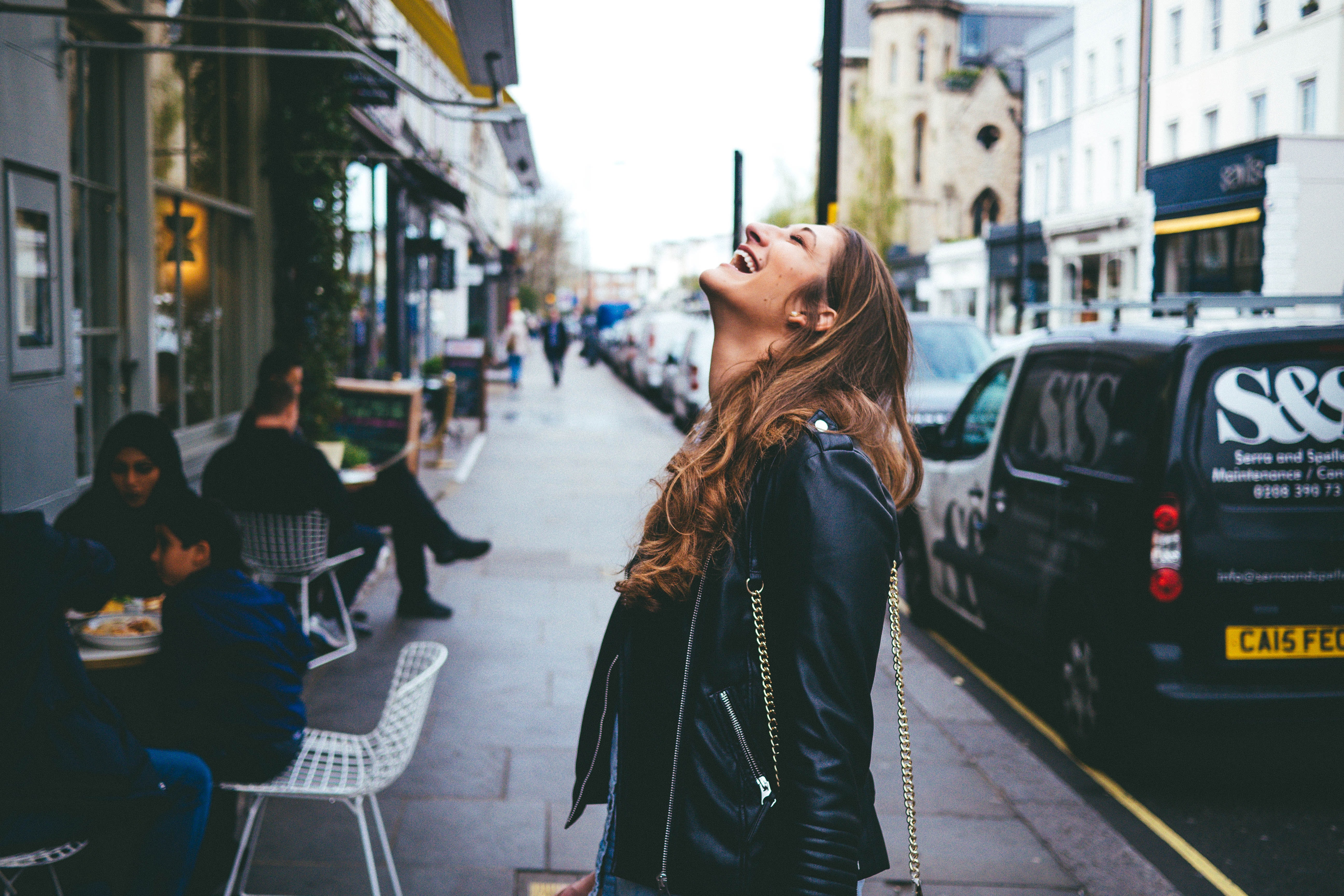 A woman in a leather jacket throws her head back and laughs on a city sidewalk