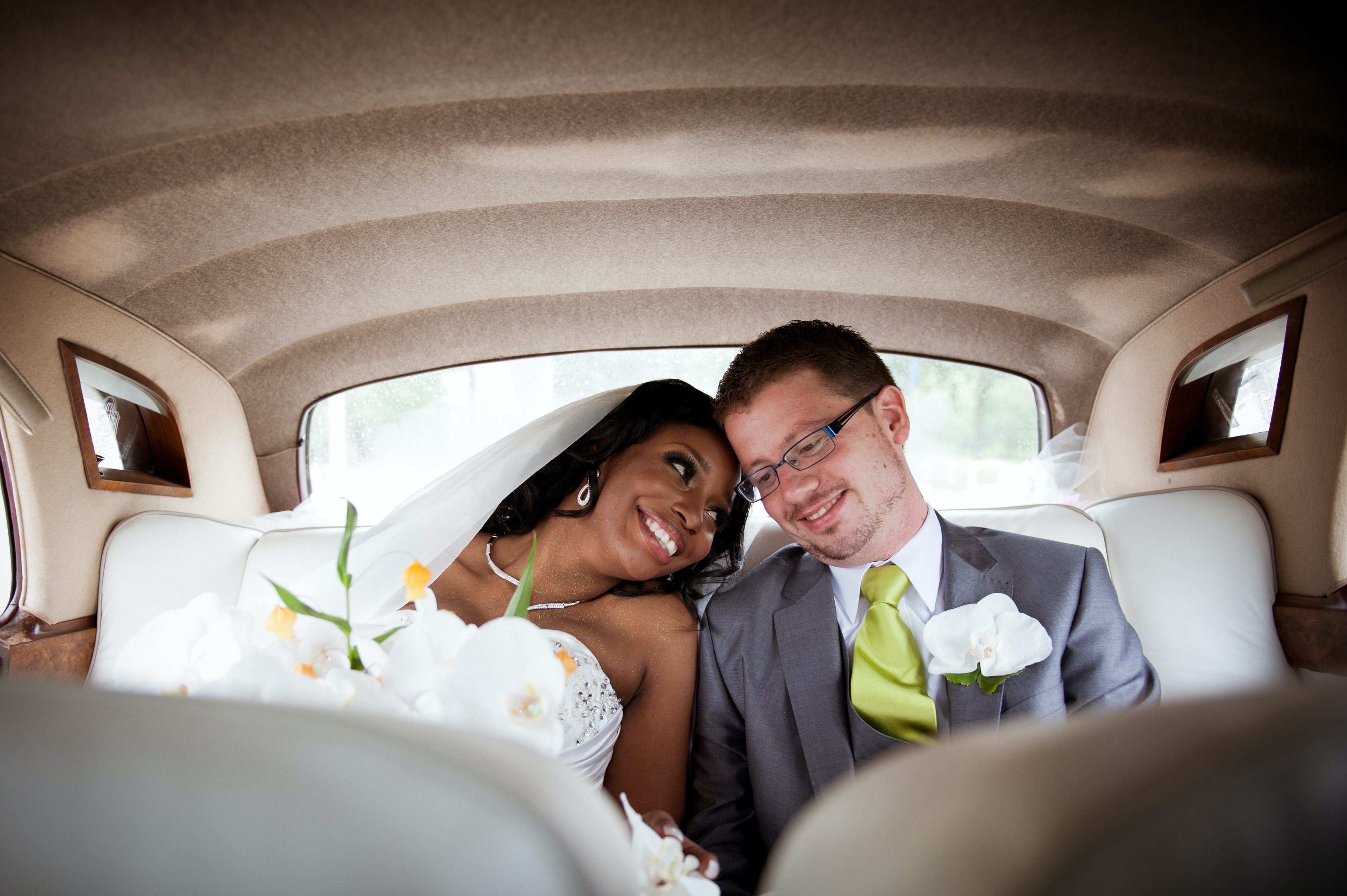 A bride and groom sitting in the backseat of a car and smiling in Amsterdam