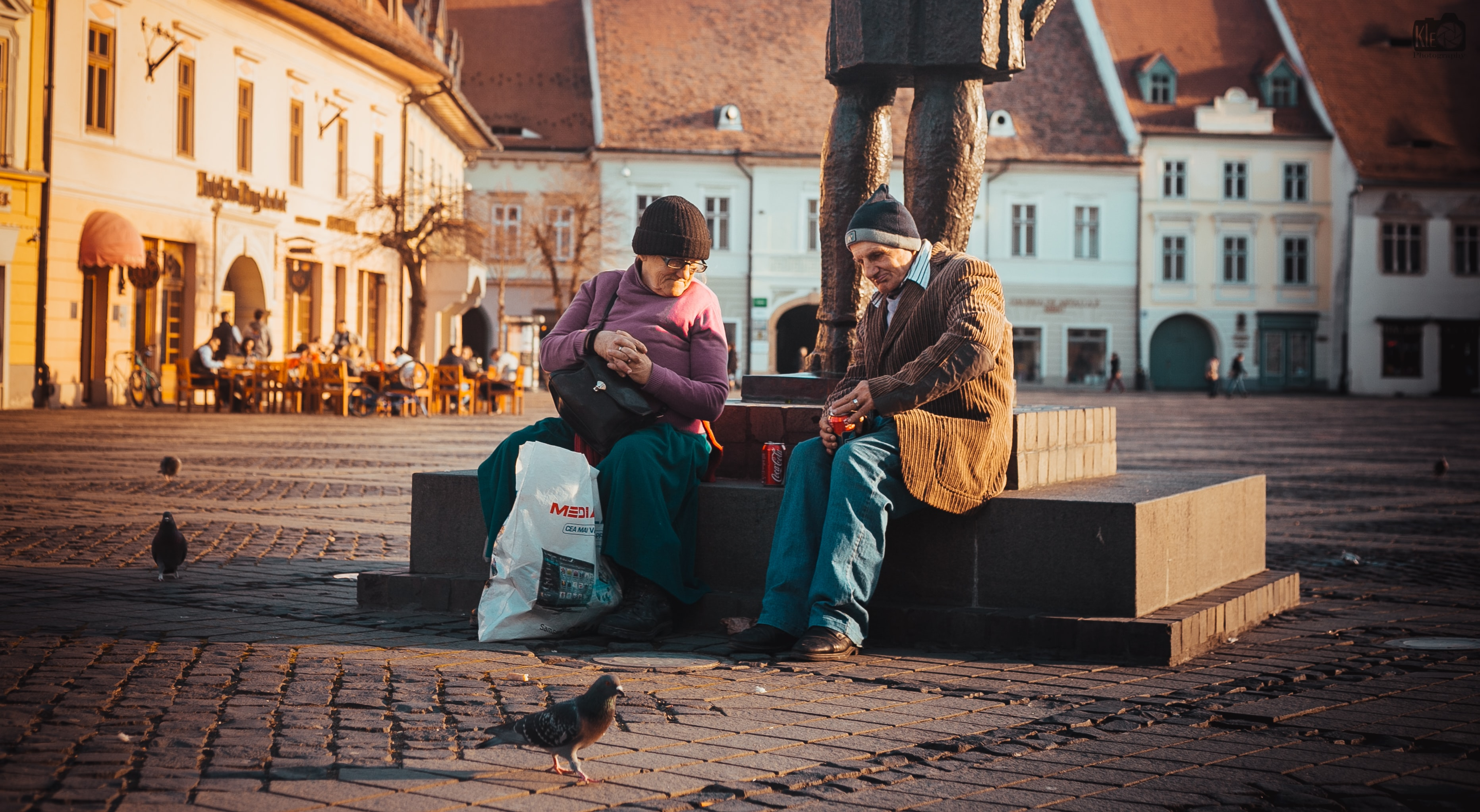 Two smiling people sitting with drinks and shopping bags aside a statue in a city square