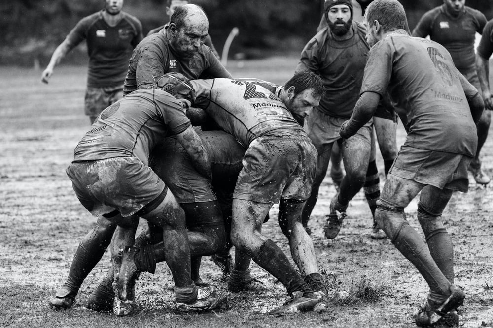 grayscale photography of group of people playing rugby on muddy field