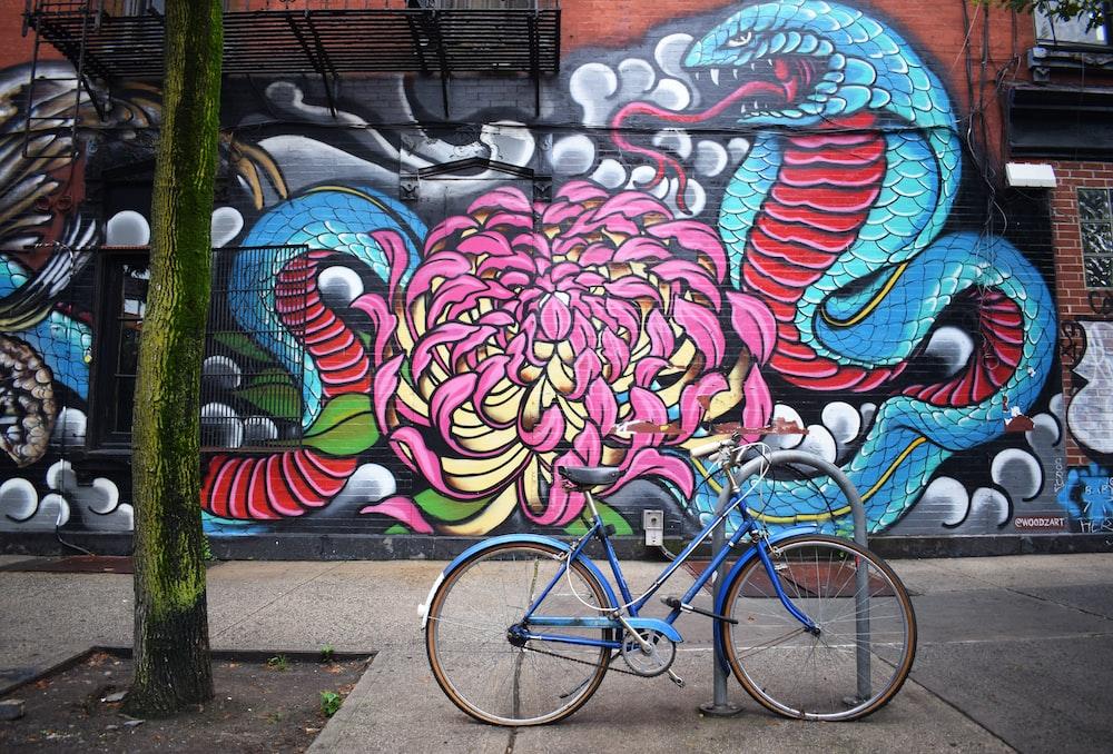 blue bicycle parked near graffiti