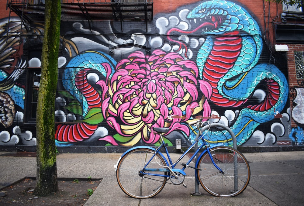 blue bicycle parked near graffiti