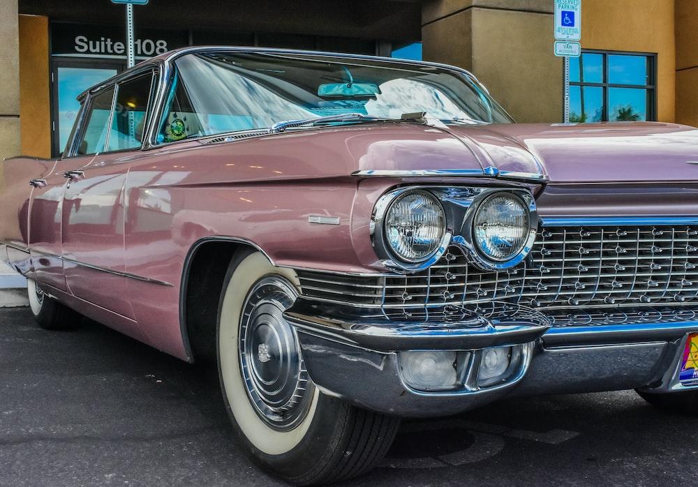 pink classic car parked near concrete building